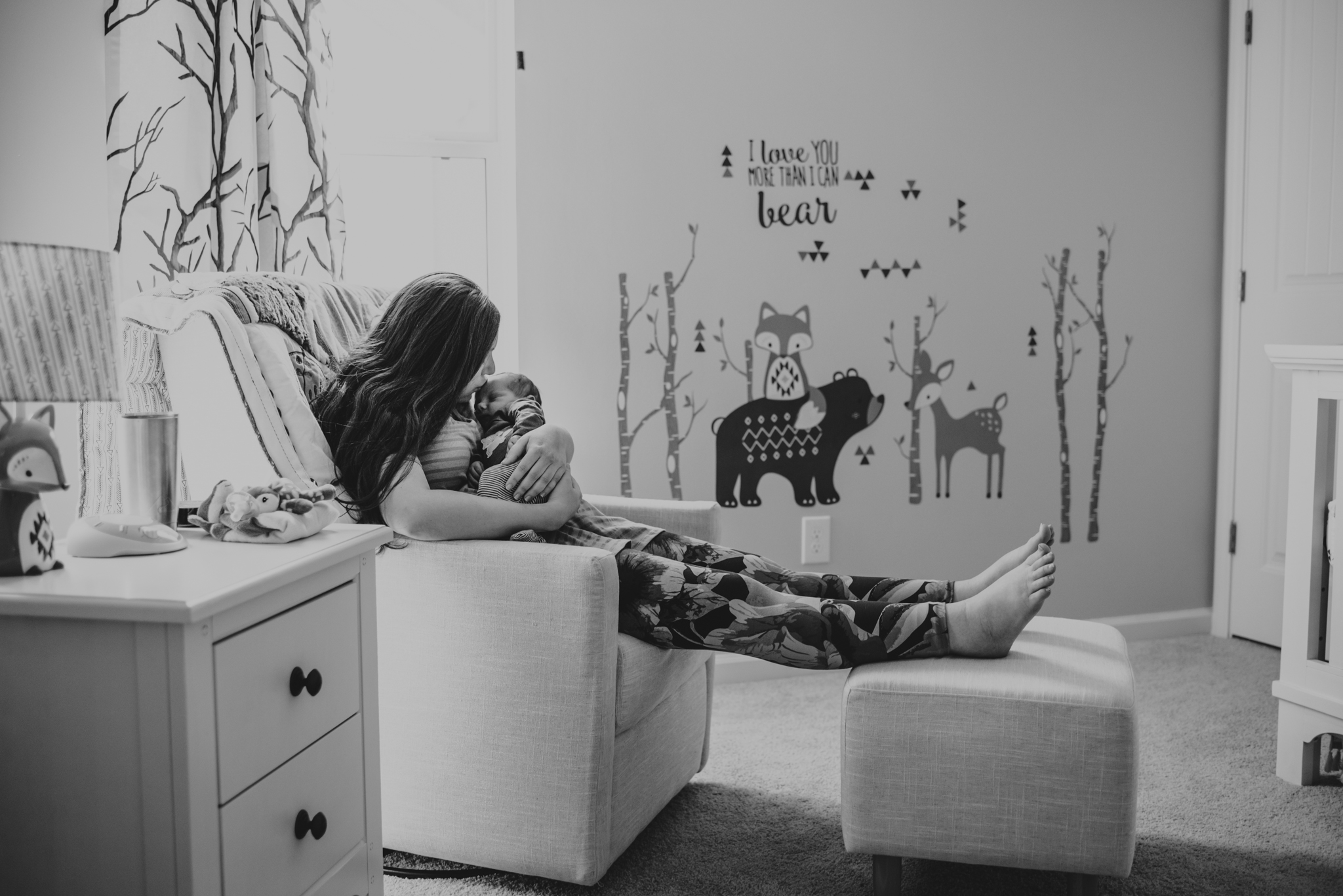 The new Mom kisses her newborn son in a chair in his nursery in Wake Forest, a black and white image by Rose Trail Images.