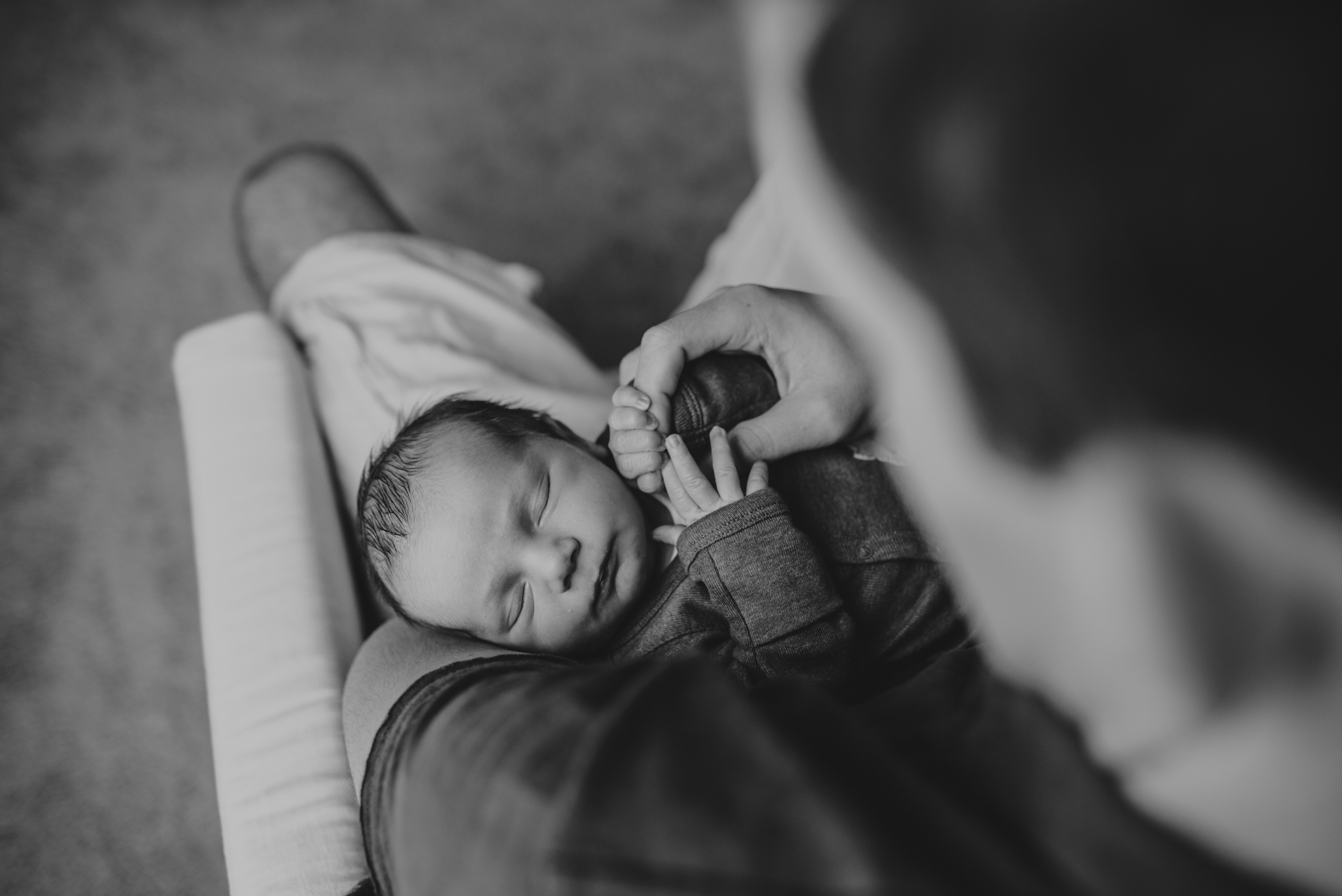 The new Dad holds his newborn son's hand in his nursery in Wake Forest, a black and white image by Rose Trail Images.