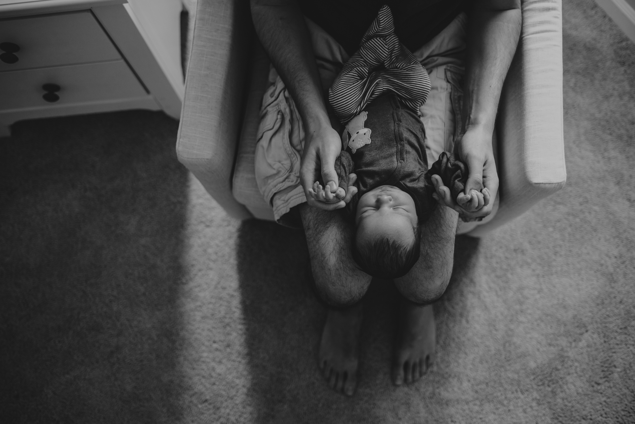 The new Dad holds his newborn son in his lap in the nursery in Wake Forest, a black and white image by Rose Trail Images.