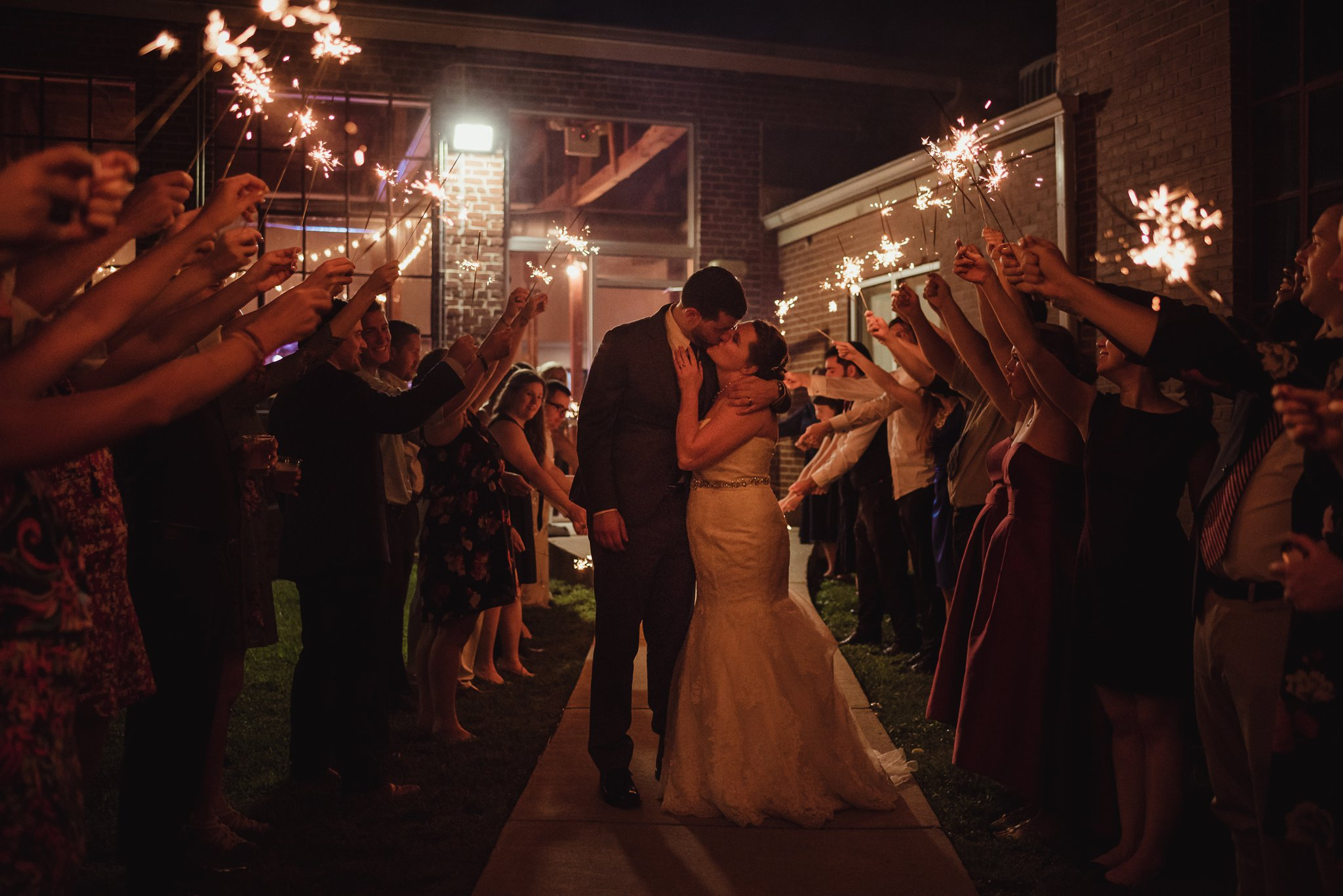 The bride and groom kissed under the sparklers during their sparkler exit at their wedding reception in Raleigh, North Carolina, pictures by Rose Trail Images.