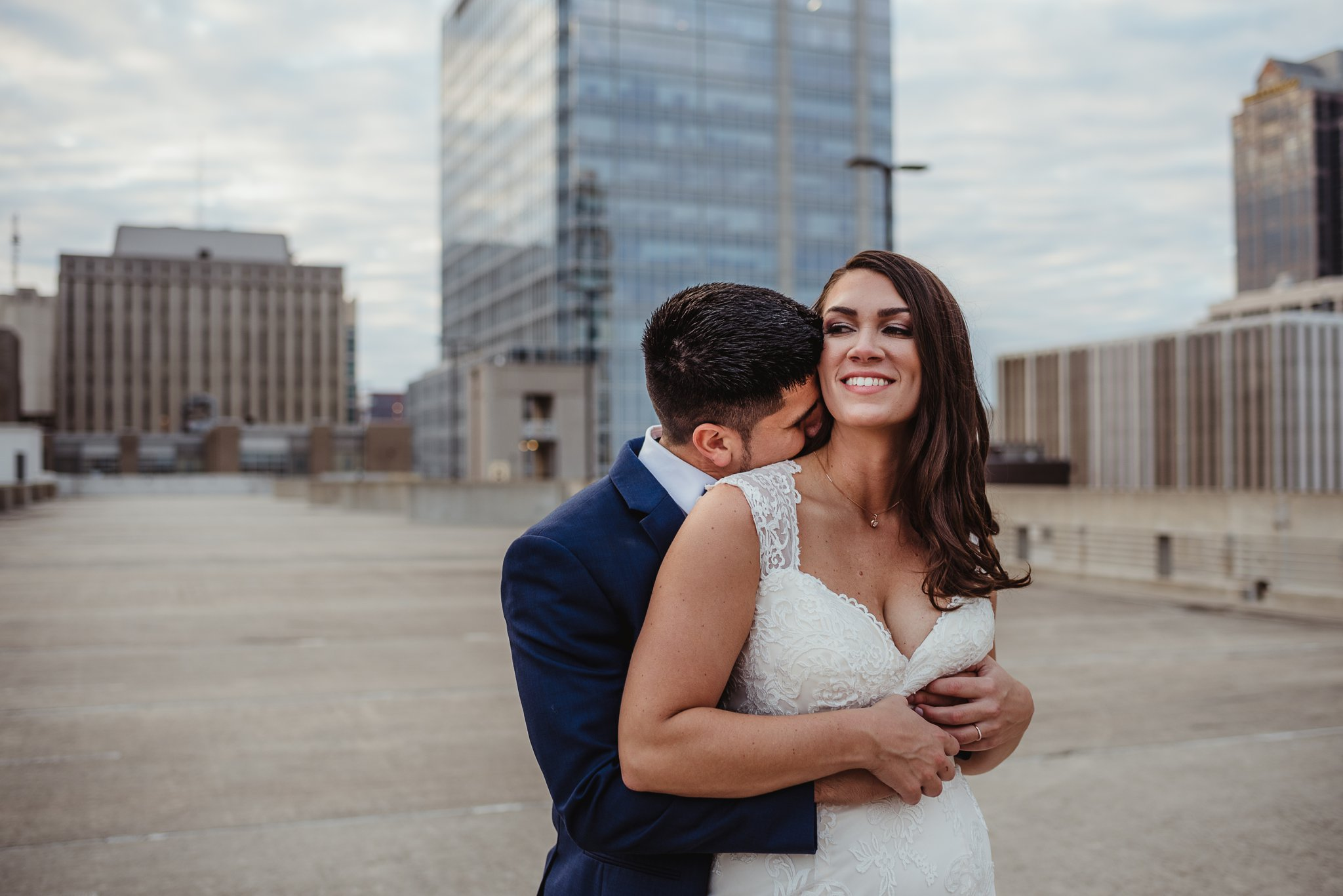 The bride and groom hugged on a rooftop after their wedding ceremony in downtown Raleigh, photos by Rose Trail Images.