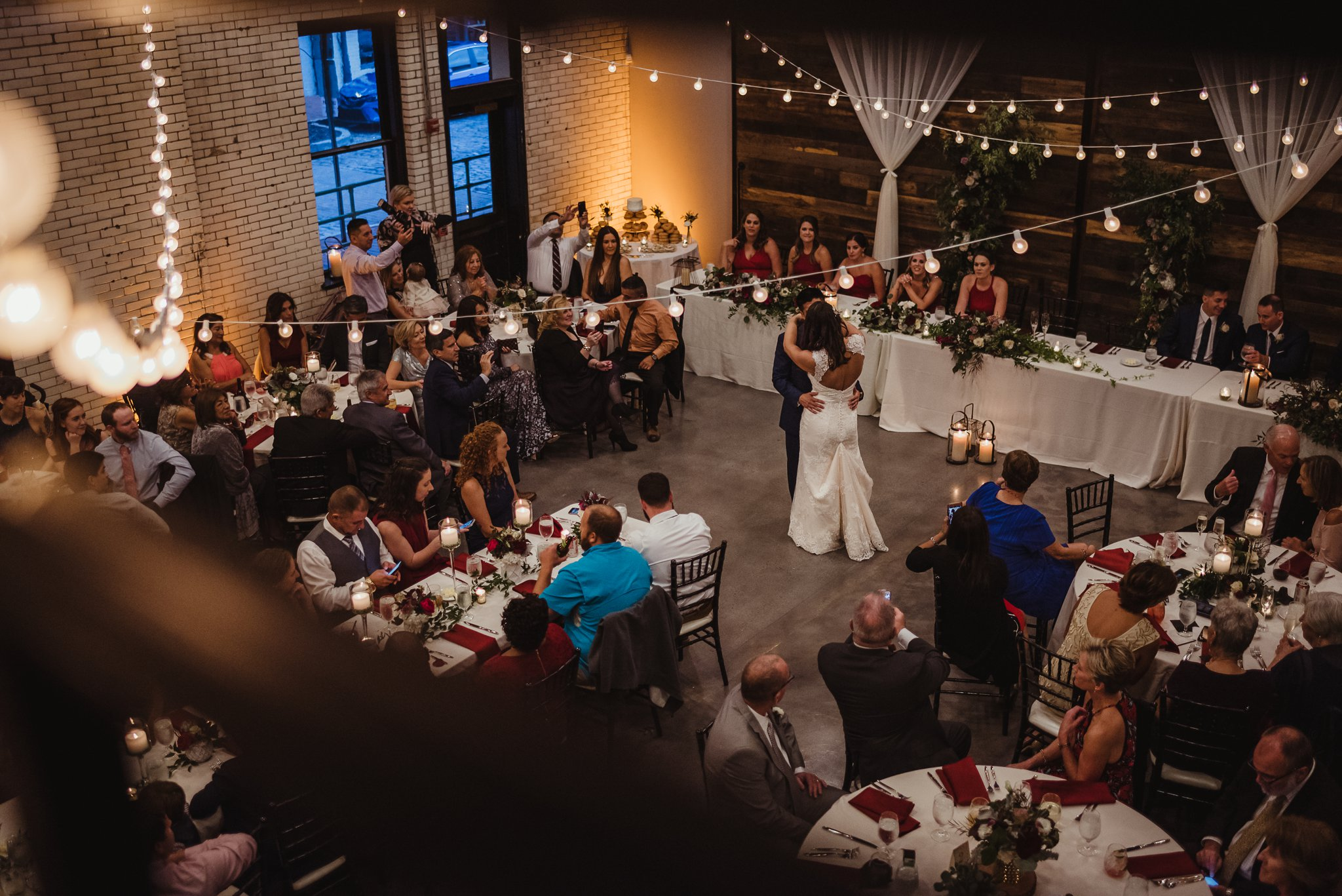 An aerial view of the bride and groom dancing their first dance together at their wedding reception at Market Hall in downtown Raleigh, photos by Rose Trail Images.