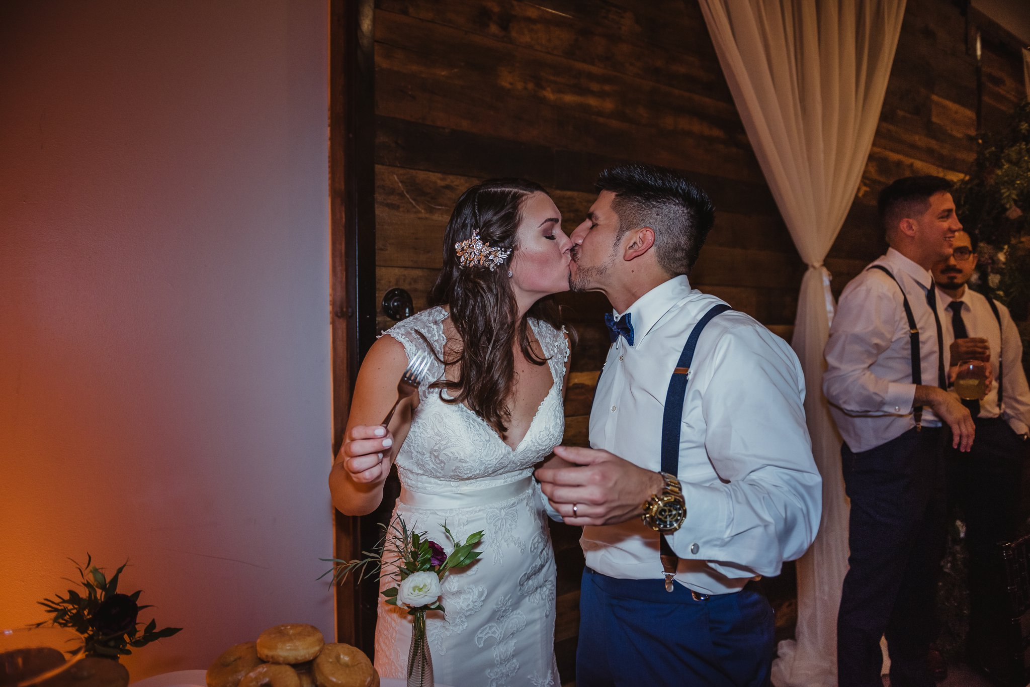 The bride and groom kissed after eating their cake at their wedding reception at Market Hall in downtown Raleigh, photos by Rose Trail Images.