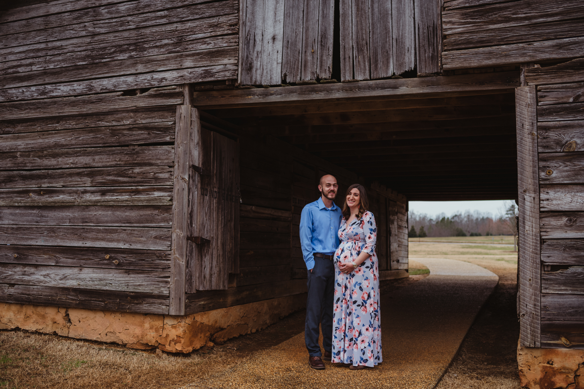 The parents to be stand under the old barn, picture taken by Rose Trail Images at Joyner Park in Wake Forest, NC.