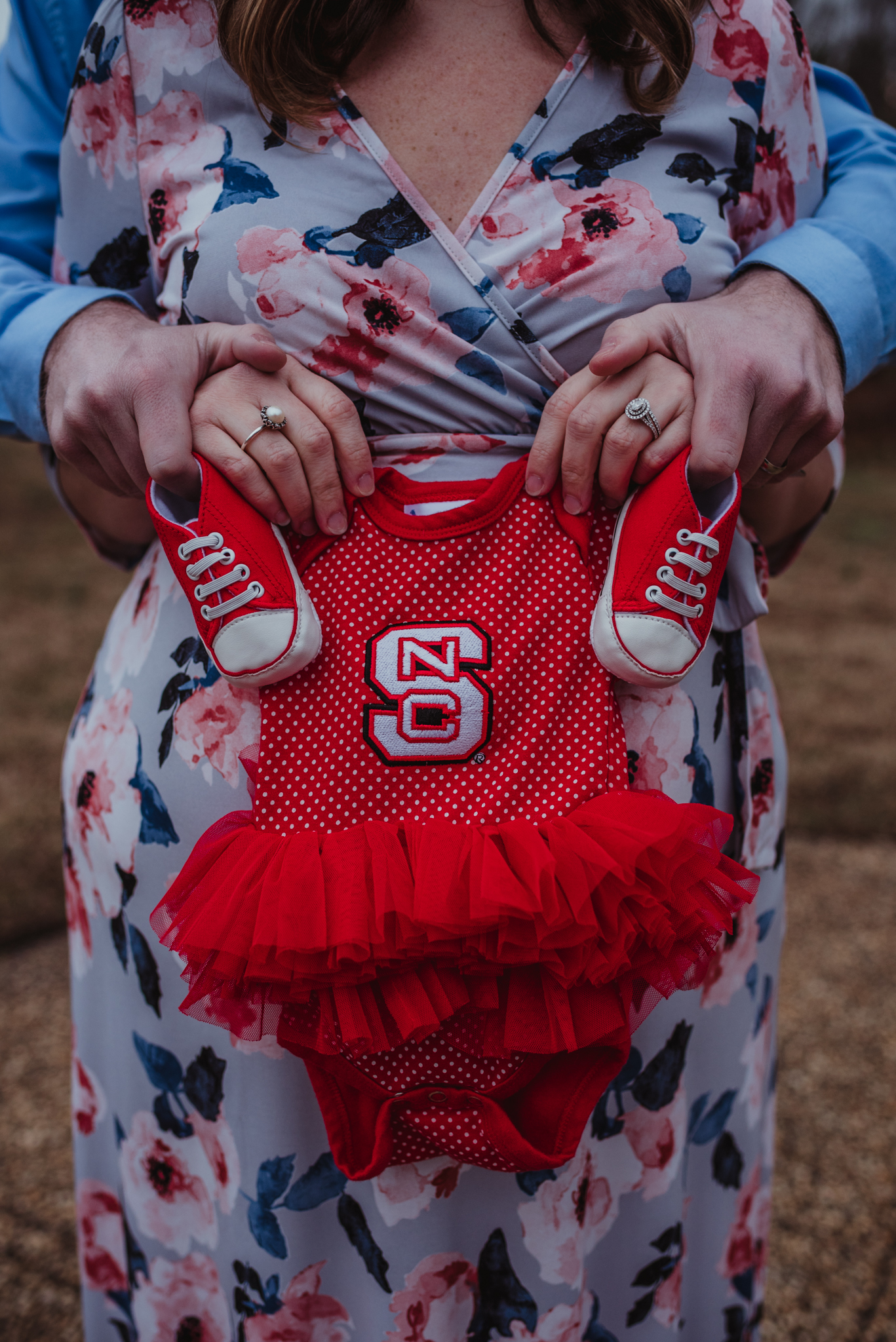 The parents to be show off their baby girl's NC State tutu and shoes, picture taken by Rose Trail Images at Joyner Park in Wake Forest, NC.