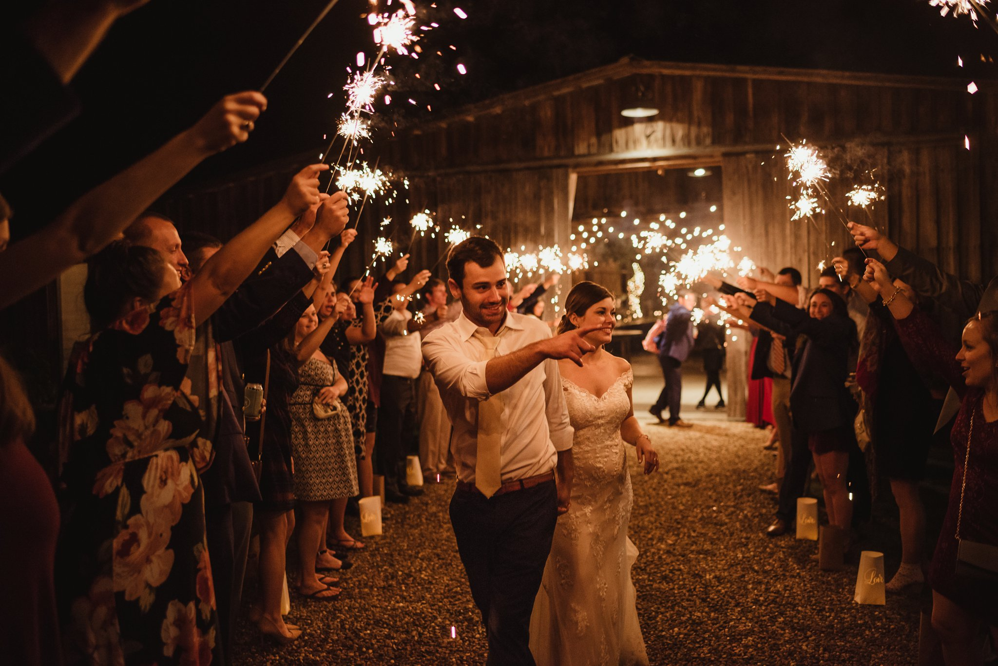 The bride and groom walk off happy during their sparkler send off after their wedding reception at the Little Herb House in Raleigh, North Carolina. Photos by Rose Trail Images.