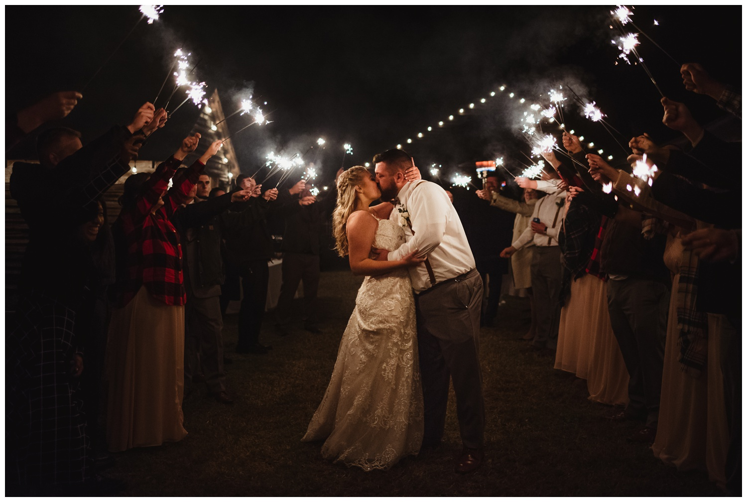 After the wedding reception at The Warren Estate, the bride and groom kissed during their sparkler exit, images by Rose Trail Images of Rolesville, NC.