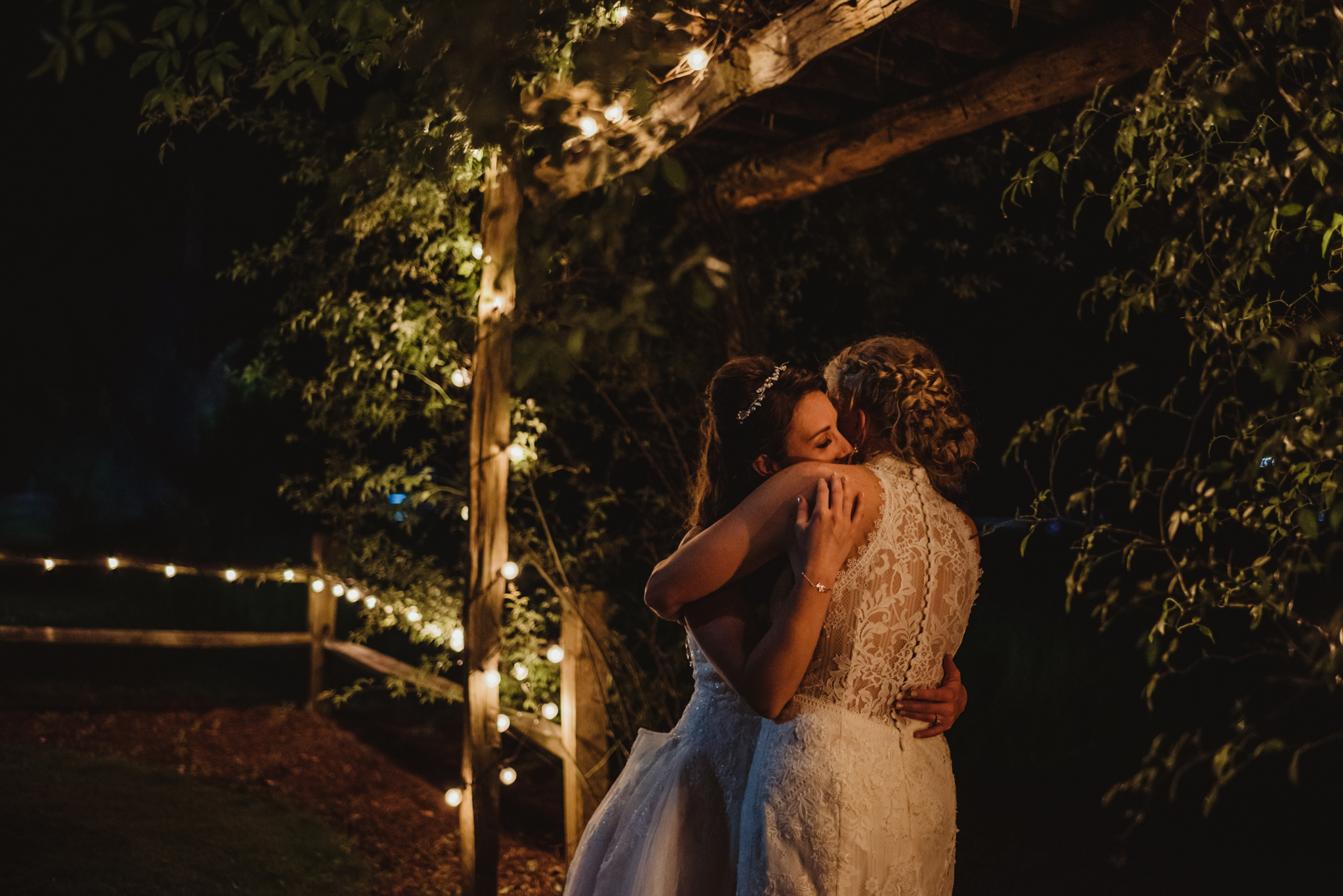 Raleigh-wedding-photographer-two-brides-snuggle-twinkle-lights-cedar-grove-acres-rose-trail-images.jpg