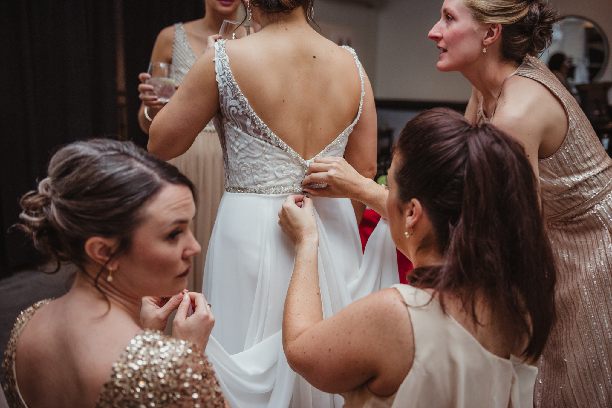 Raleigh-wedding-photographer-bride-getting-ready-girls-help-to-bustle-rose-trail-images.jpg