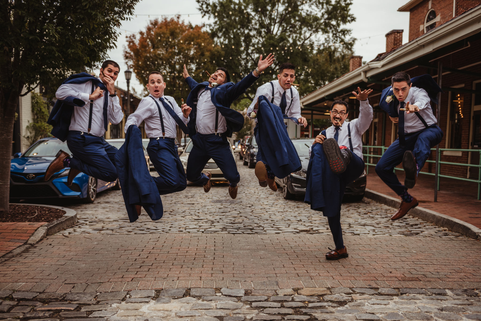 Raleigh-wedding-photographer-groomsmen-jumping-market-hall-rose-trail-images.jpg