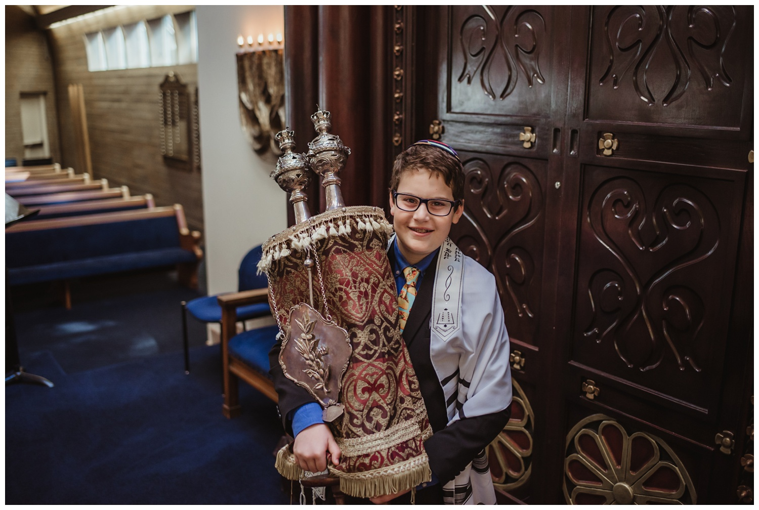 The bar mitzvah boy posed with the Torah in front of the ark at Temple Beth Or in Raleigh, NC, picture by Rose Trail Images.