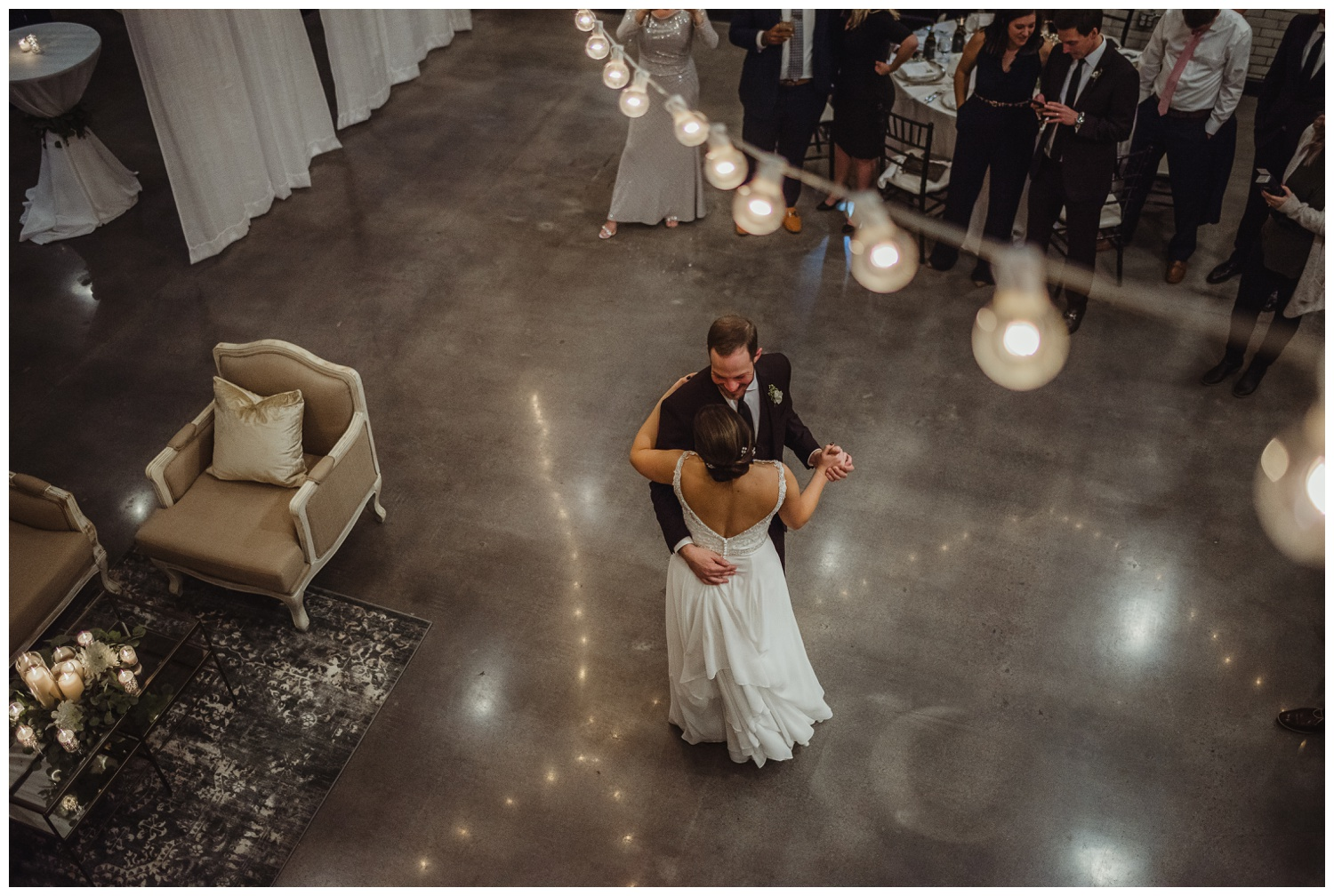 The bride and groom dance their first dance under the market lights in downtown Raleigh, photos by Rose Trail Images.