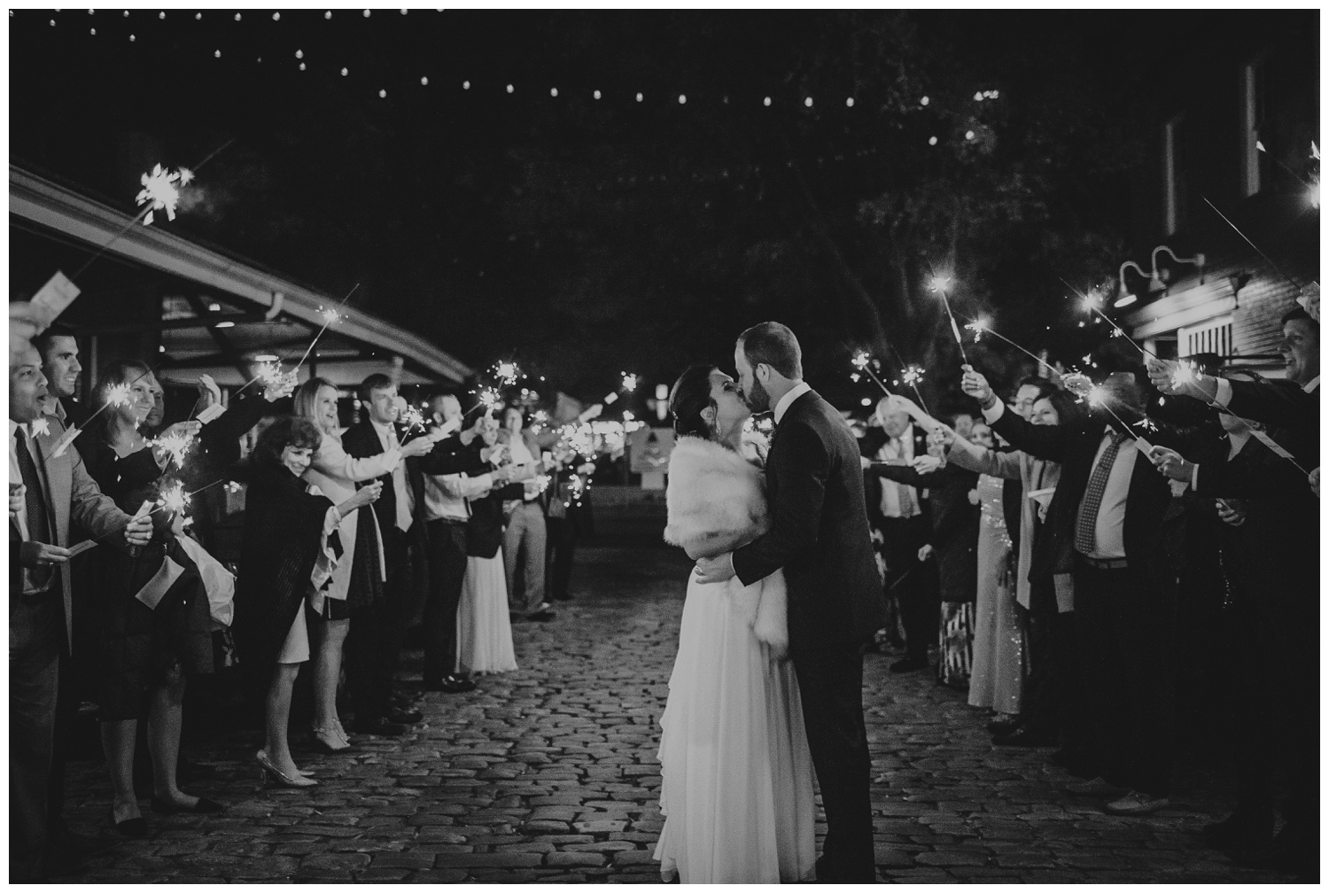 The bride and groom kissed under the sparklers for their exits their wedding reception in downtown Raleigh, photos by Rose Trail Images.