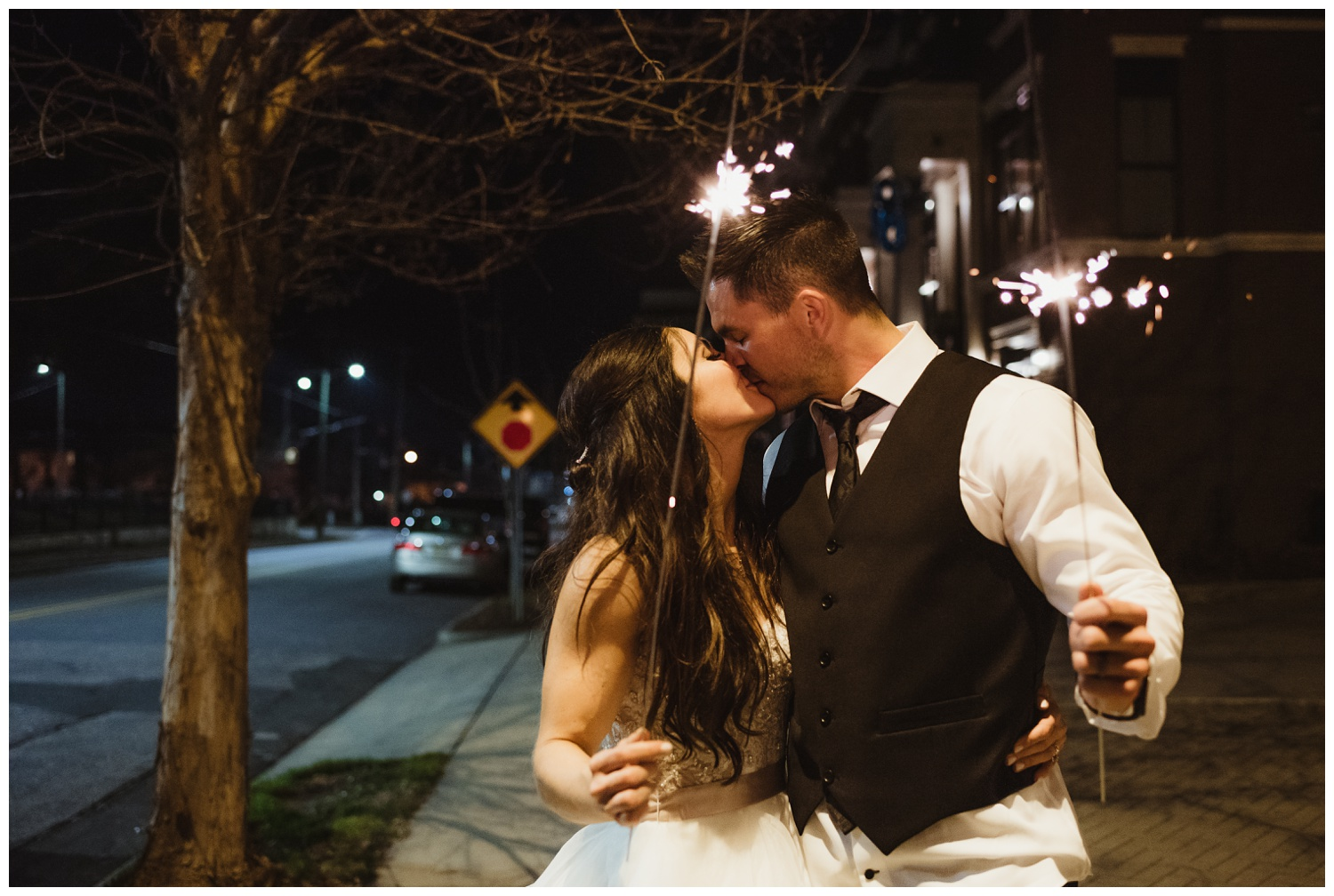 The bride and groom kiss with sparklers after their wedding reception at All Saints Chapel in Raleigh, North Carolina, pictures by Rose Trail Images.
