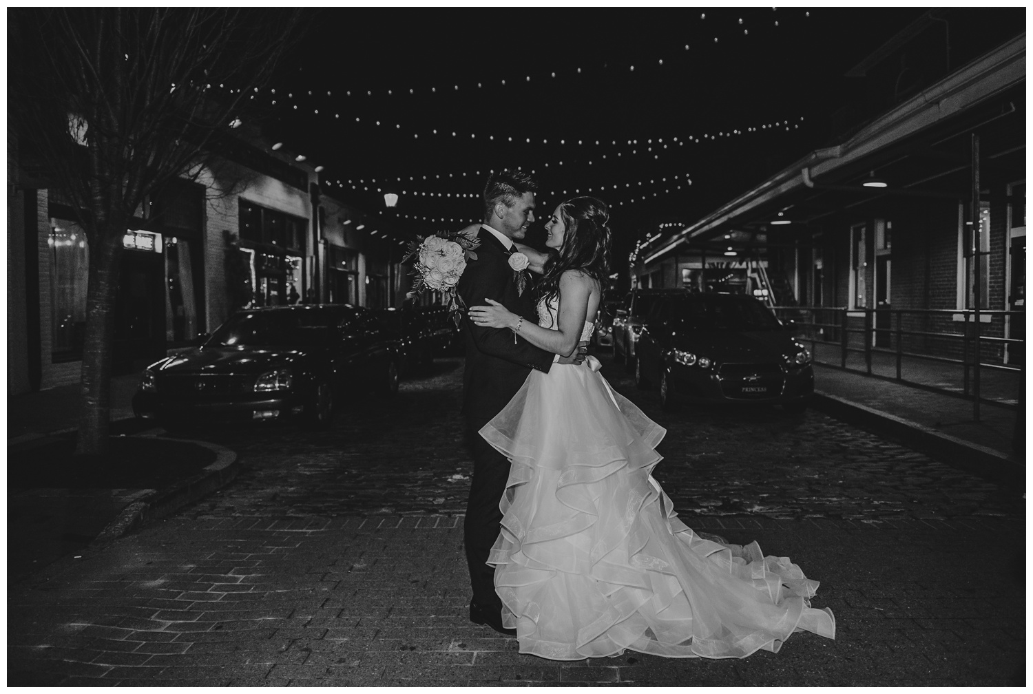 The bride and groom pose for a night portrait at Raleigh's Market Hall after their wedding ceremony, picture by Rose Trail Images.