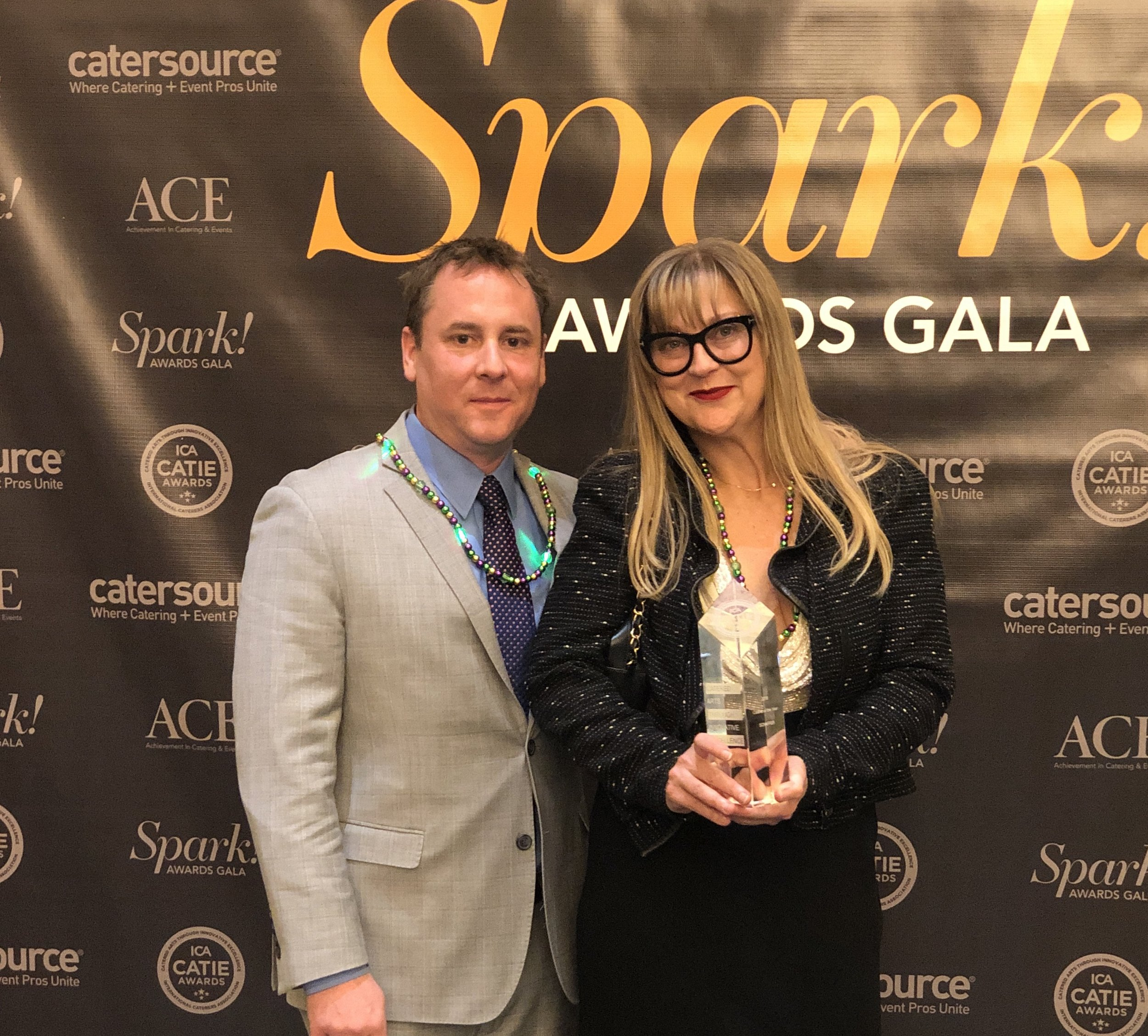 2019 Caterer of the Year! Proud owners, Kathleen & Charlie Schaffer take home the big prize of the night in New Orleans, Mardi Gras beads and all!