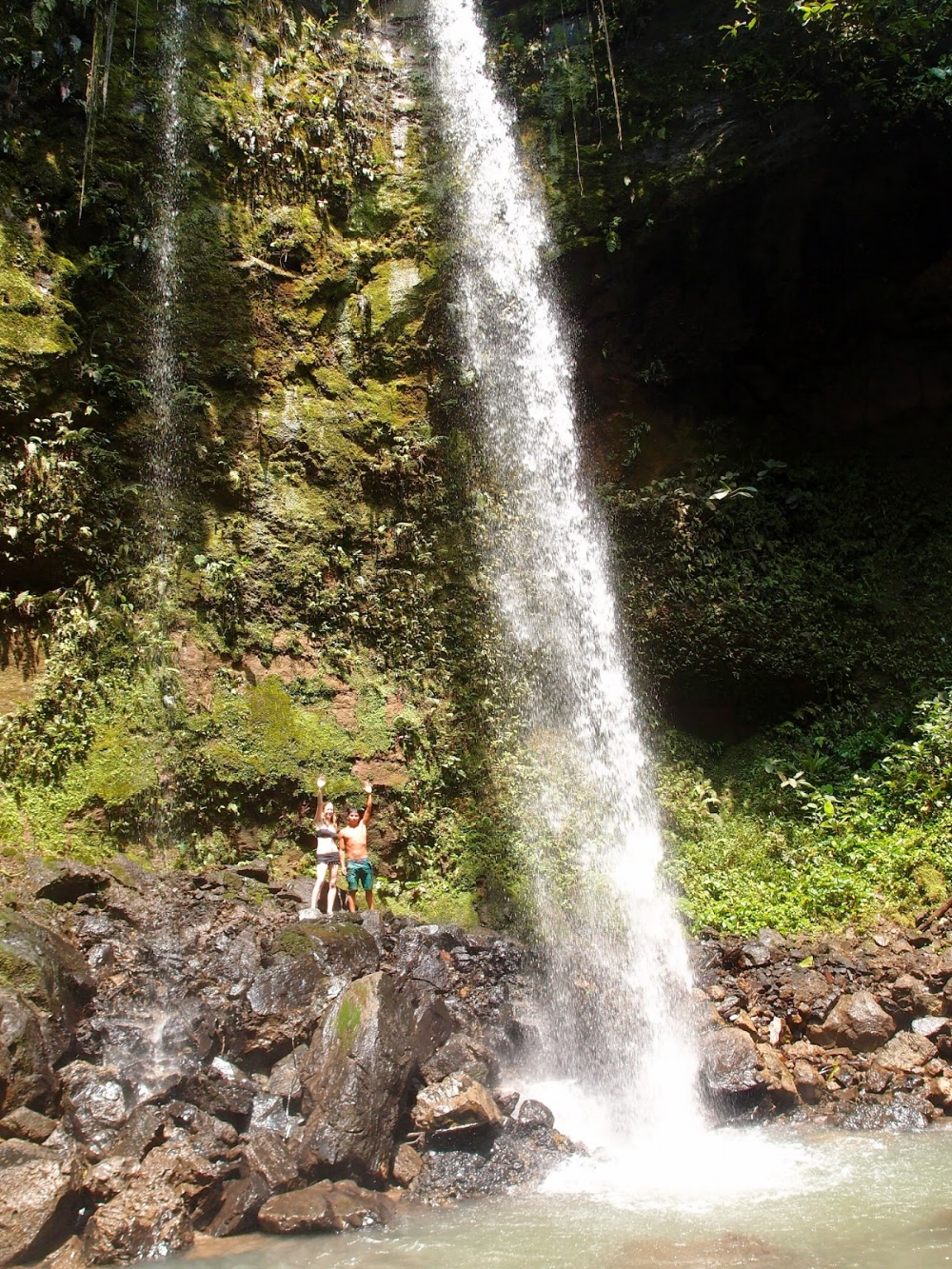 Pegonka and Laura at a sacred waterfall in the remote Huaorani territory of the Ecuadorian Amazon