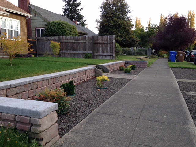 Concrete retaining wall blocks with caps. Front beds are landscaped with crushed gravel.