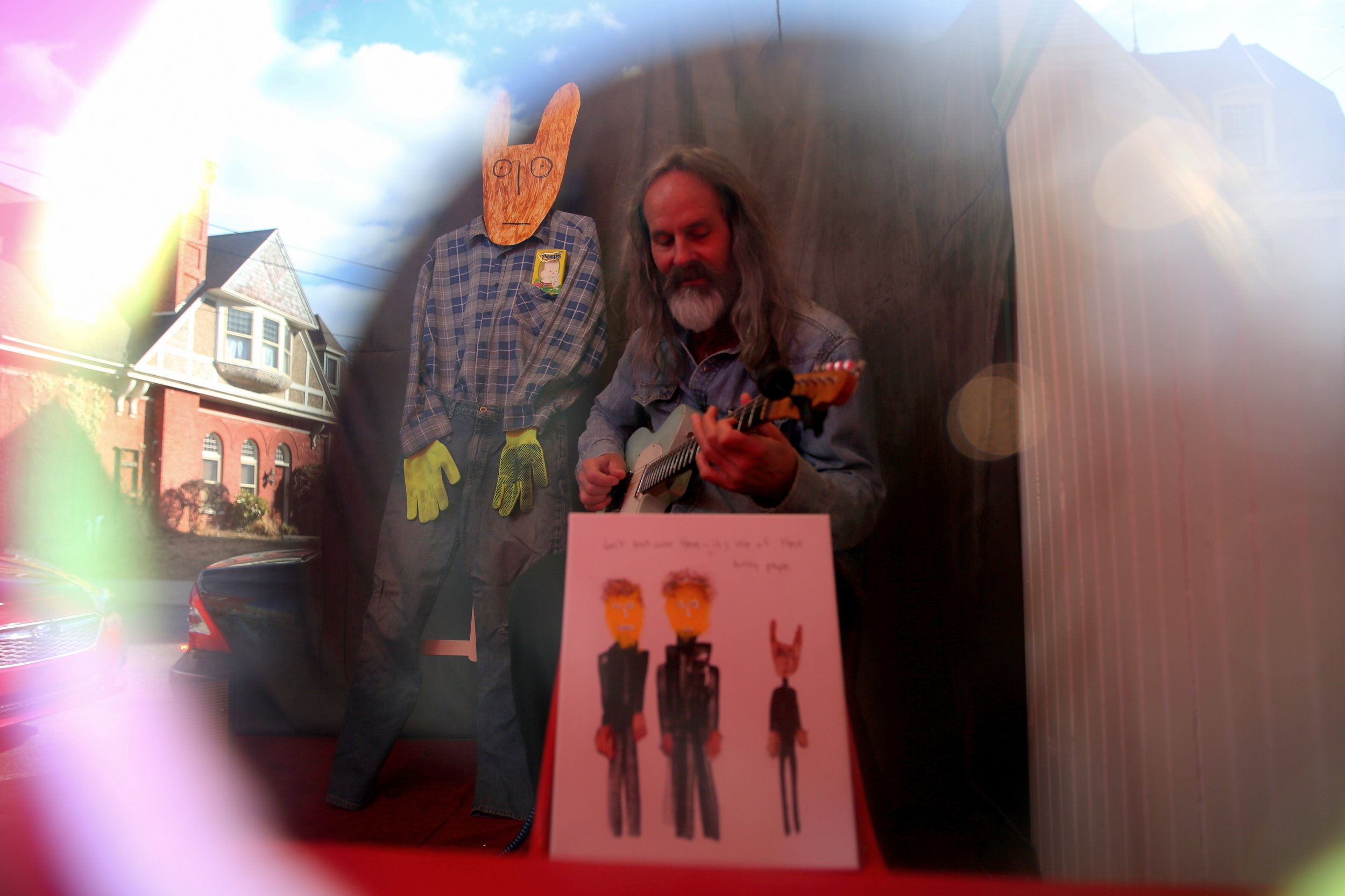 Artist and Musician, Scott Bookman, playing guitar in the peep show next to his artwork.
