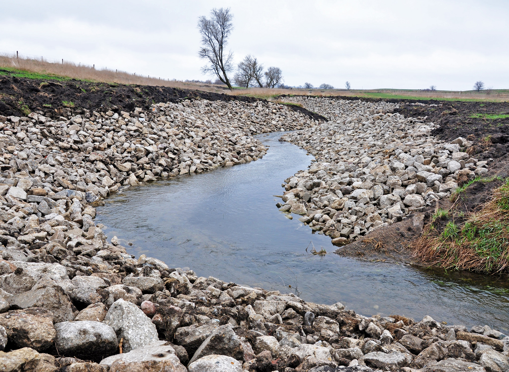 A newly completed stream bank stabilization project near Black Hawk Lake in Sac County uses rip rap to hold key points of the stream bank in place.