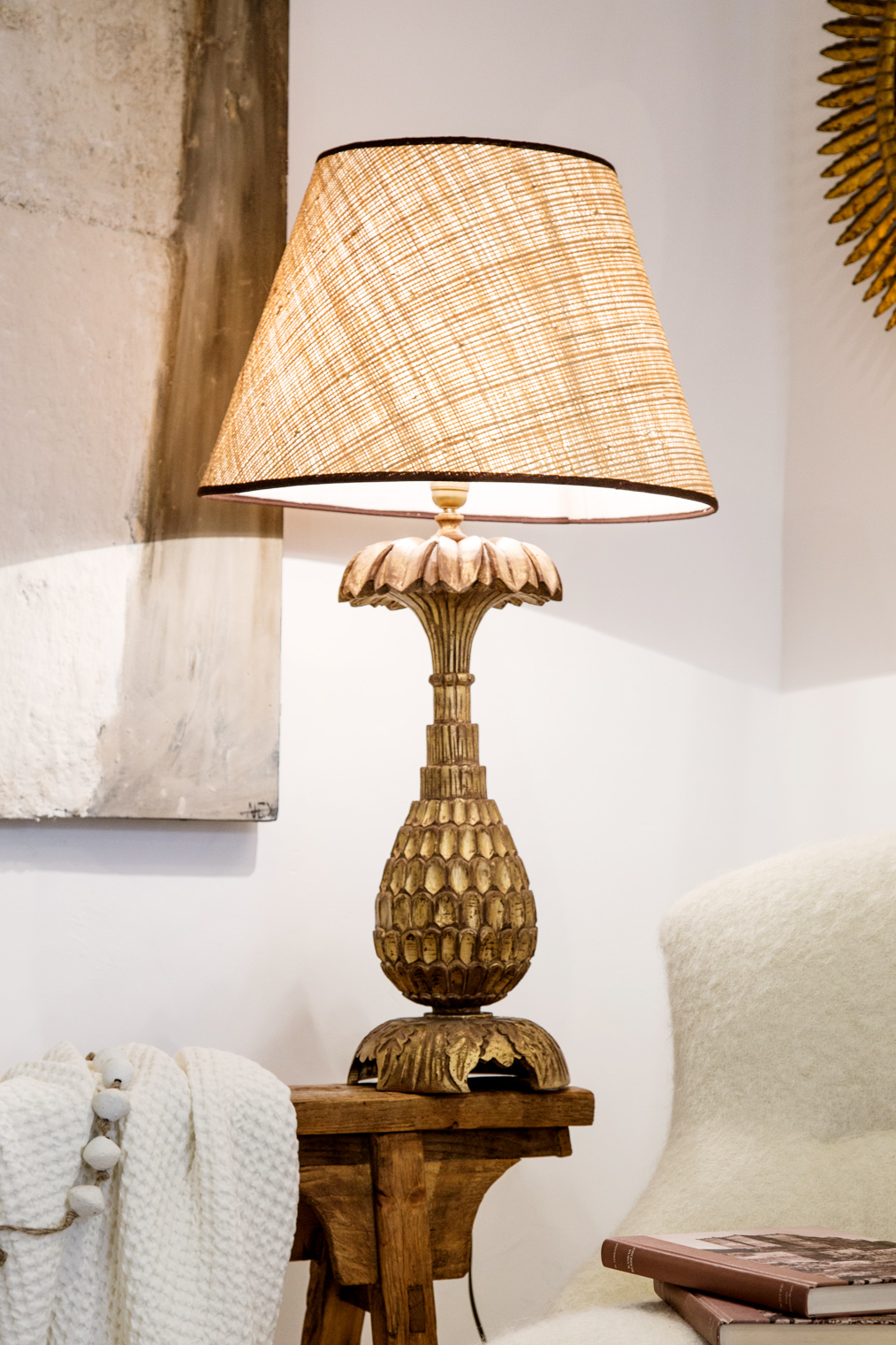 Lampe de table en bois sculpté, finition doré mat, abat-jour en rafia