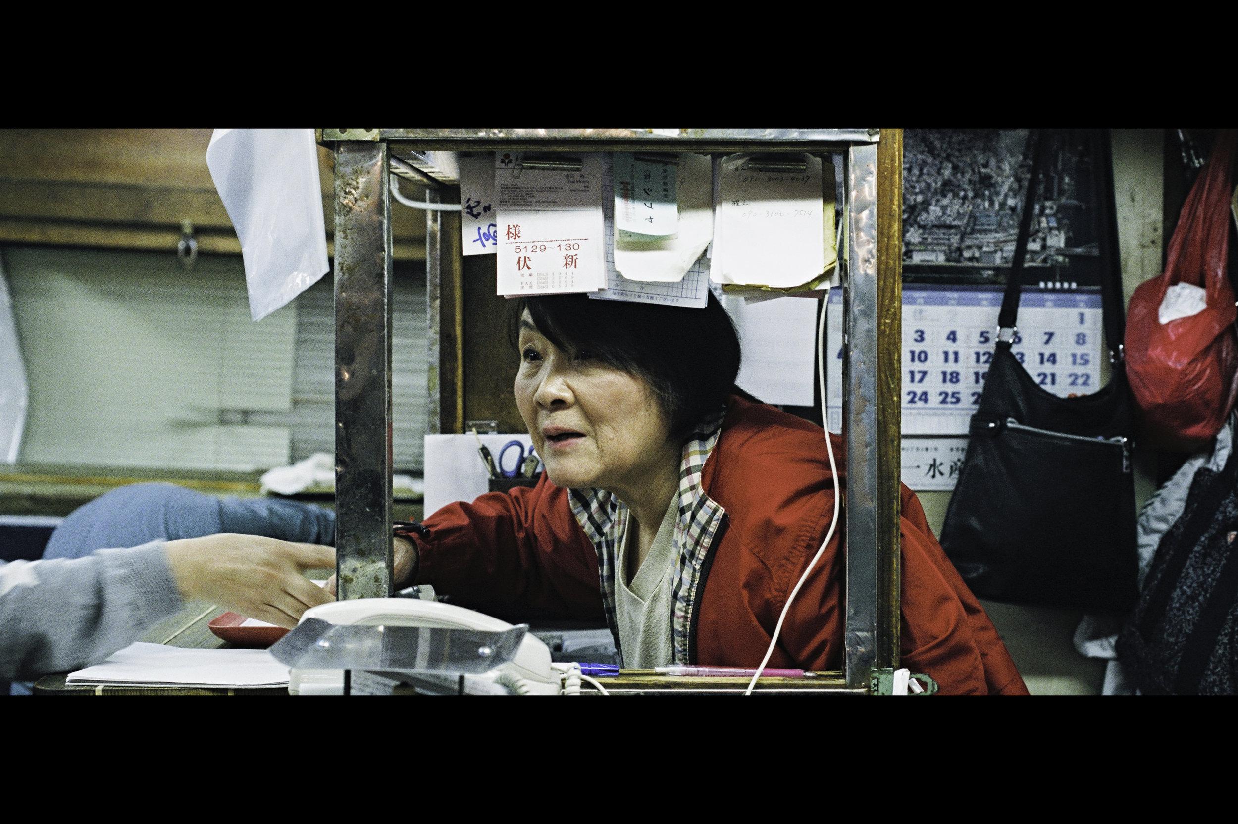 woman-tsukiji-fish-market-vendor-booth