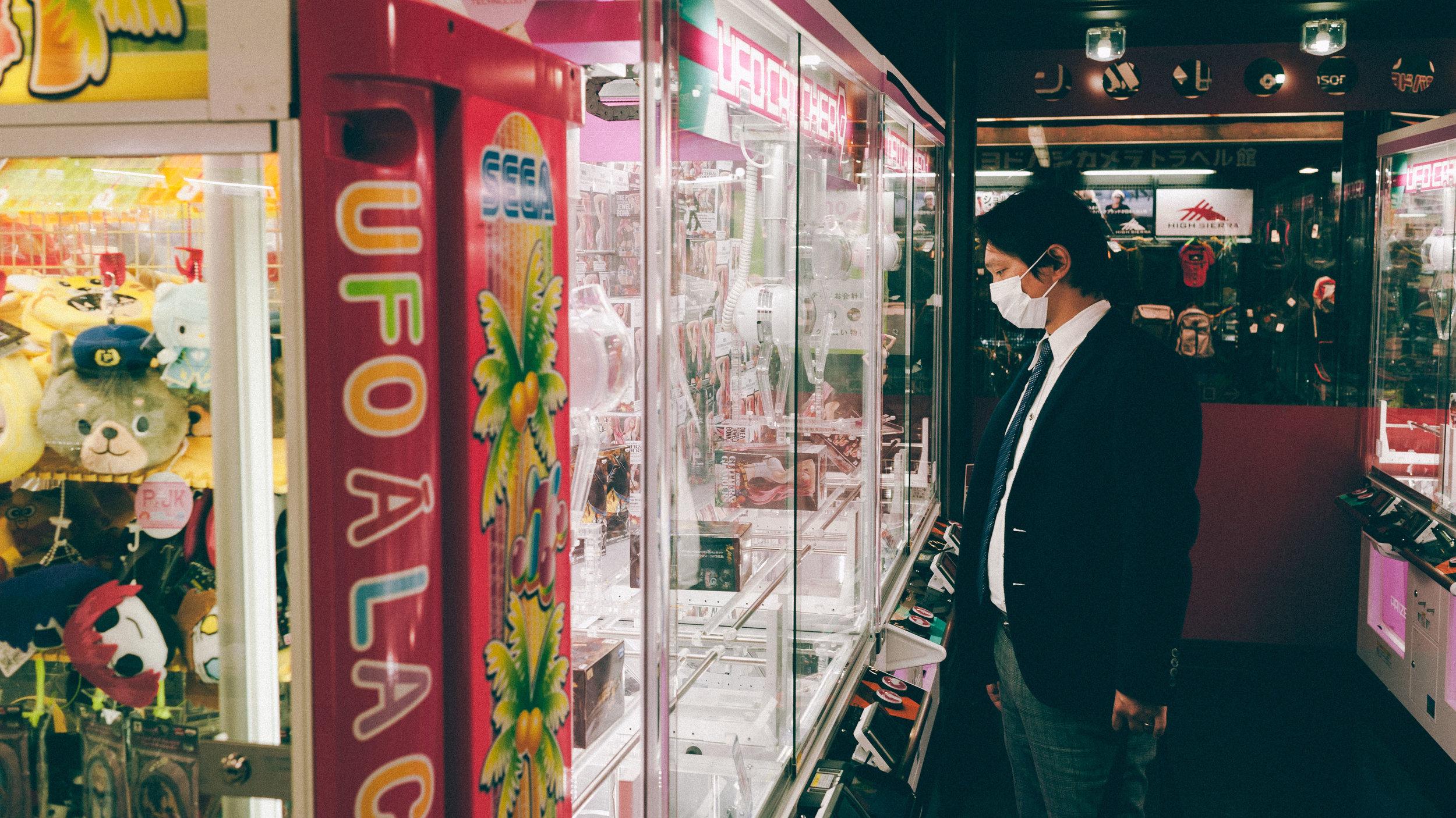 man-playing-claw-game-tokyo-japan.jpg