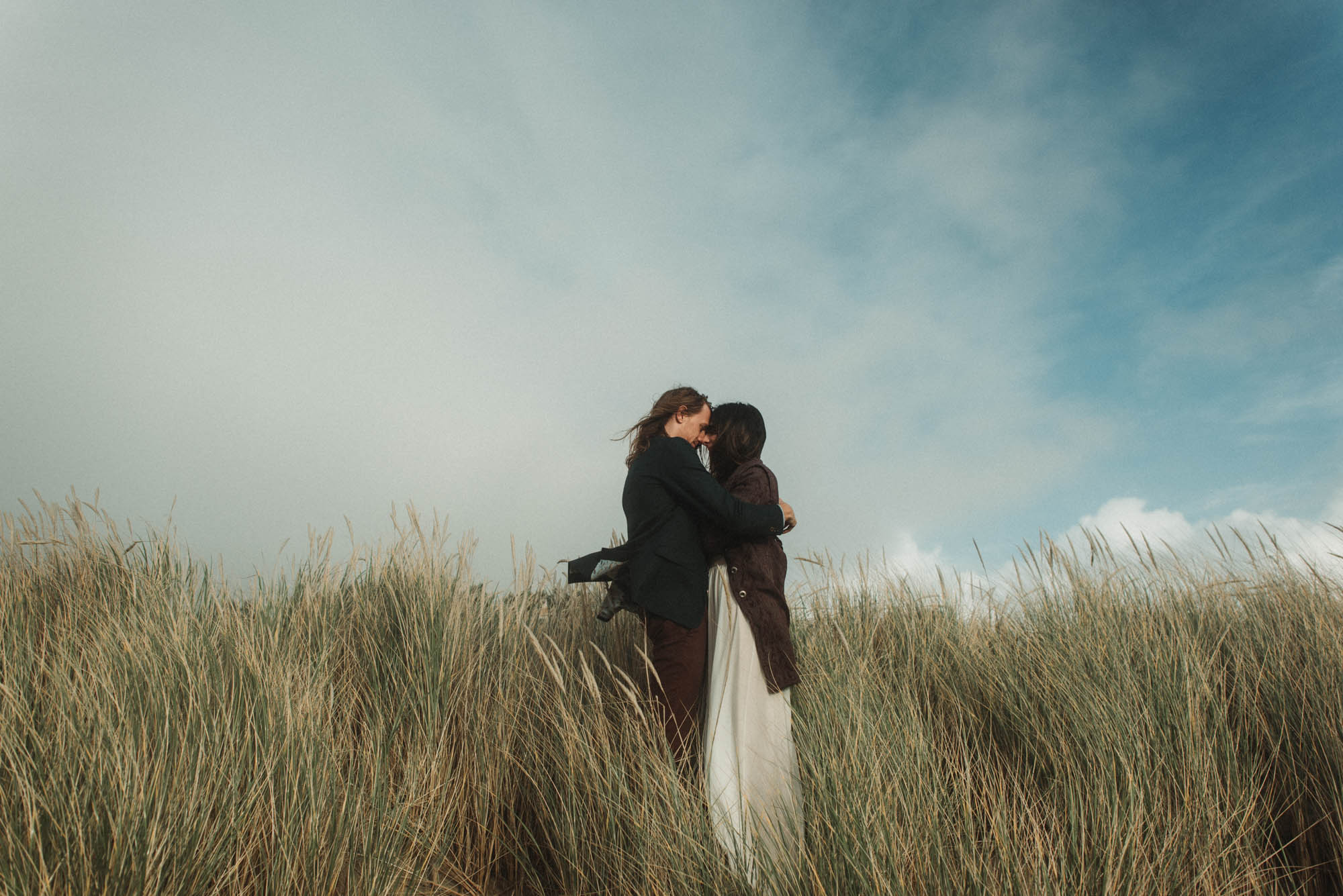 Bride and Groom portrait in tall grass on the coast