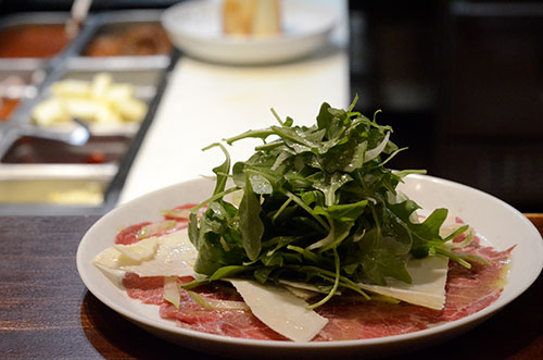 Fresh arugula, parmesan and salami antipasto dish being prepared for Al Volo's catering menu.