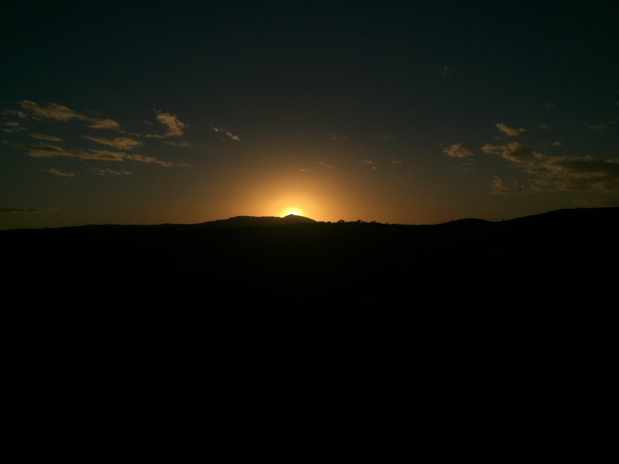 Sun setting over the desert hills