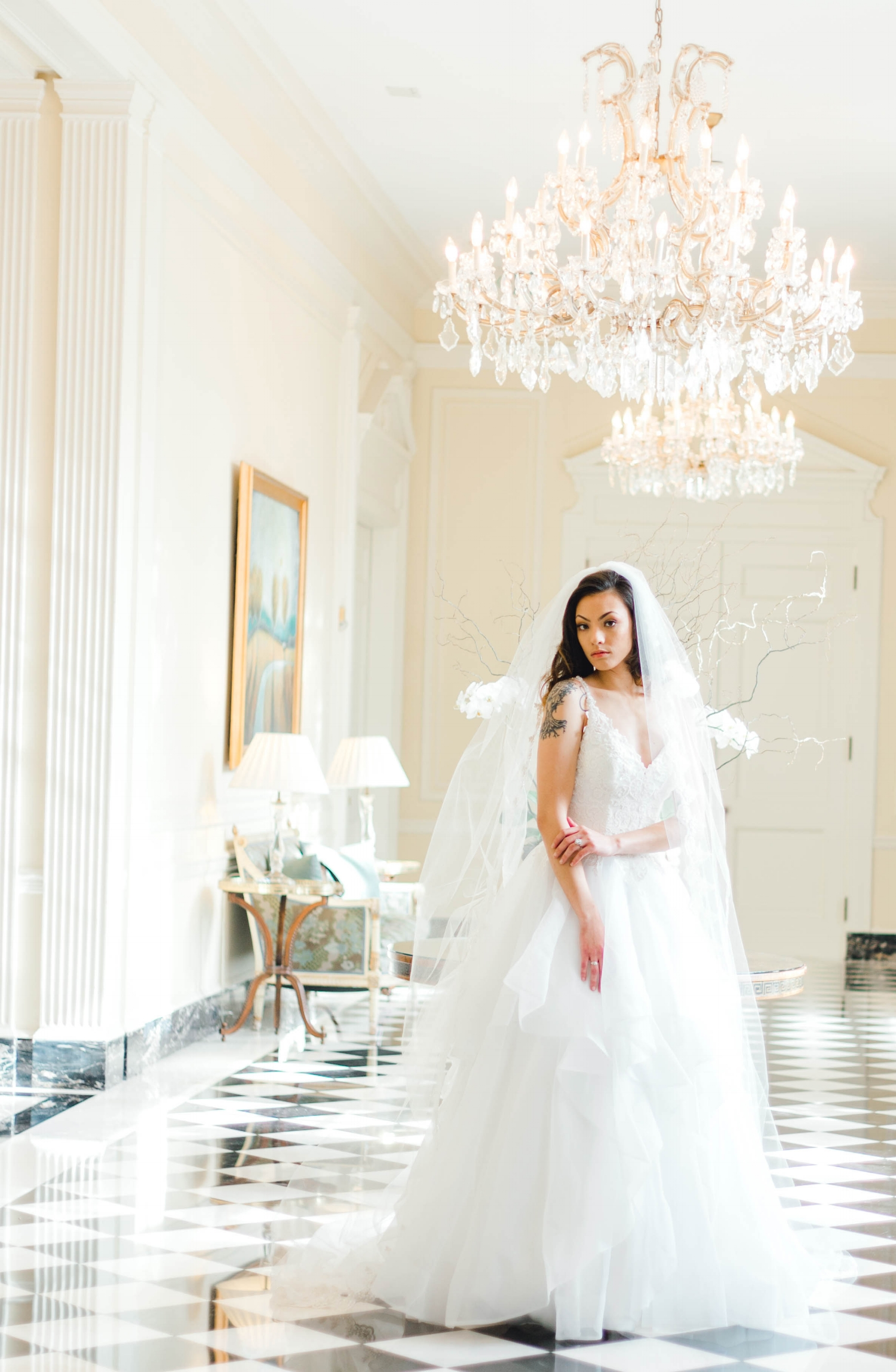 A bride on a checkerboard floor with crystal chandeliers.