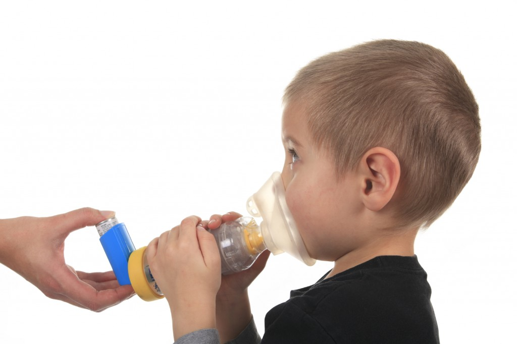 A child using his inhaler with a spacer