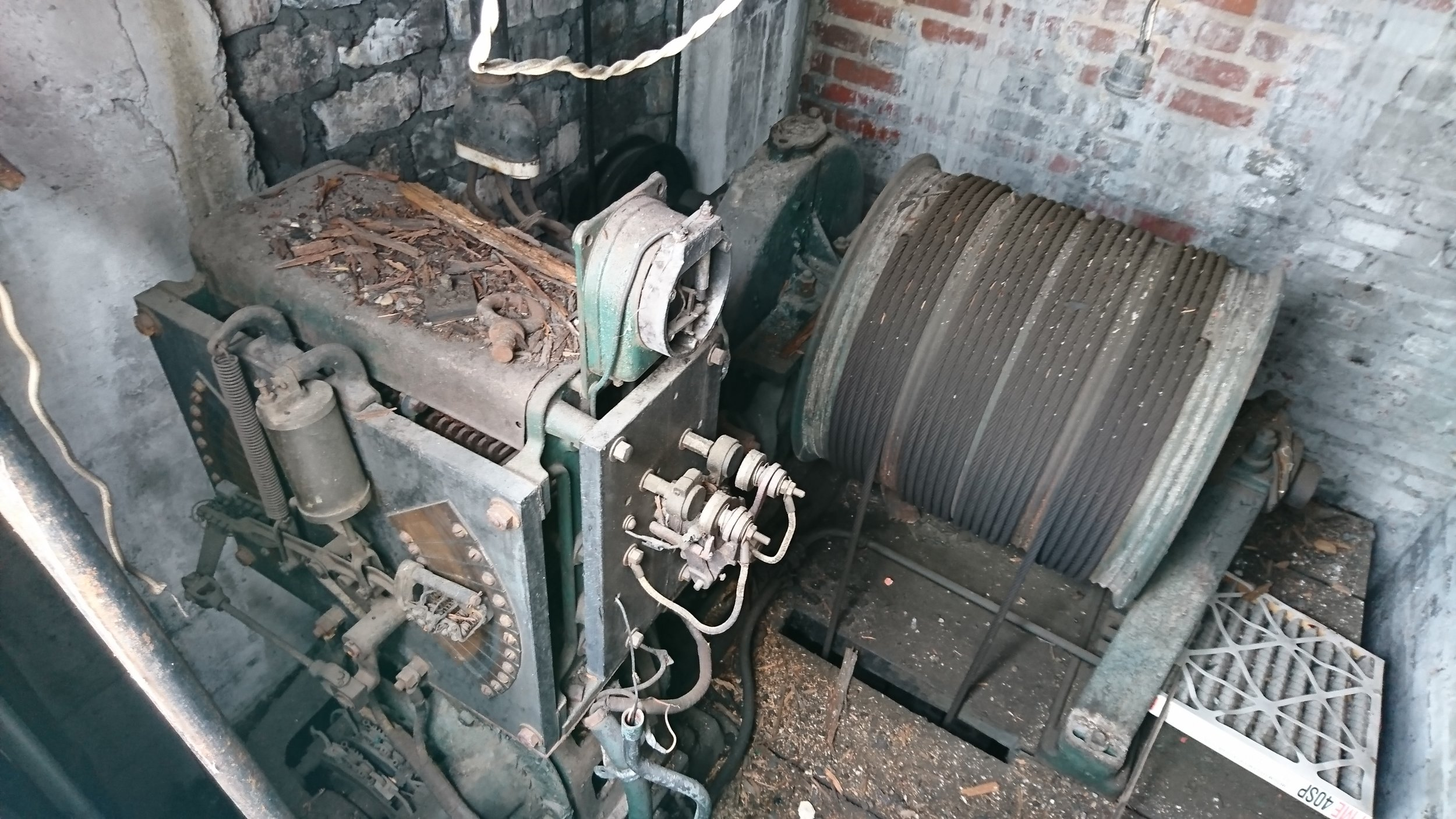 Original elevator machinery and future home of  The Corner Office 's private phone room.