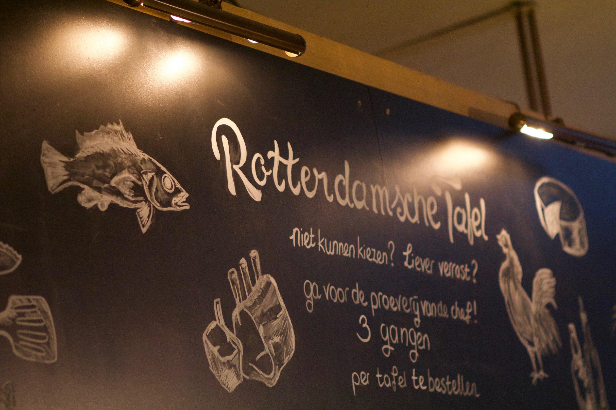 - De Rotterdamsche TafelKomt u ons met 4 of meer personen vergezellen? Dan is de Rotterdamsche tafel voor u al mogelijk! Deze variant van shared dining is ideaal voor (middel)grote gezelschappen. Het idee is dat men samen deelt, dineert en geniet van een scala aan gerechten. In één of meer gangen presenteren wij een diversiteit aan gerechten, die geserveerd worden op borden en schalen.Drie gangen Rotterdamsche Tafel: € 44,50Voorgerecht € 14,50Hoofdgerecht € 28,50Nagerecht € 7,50