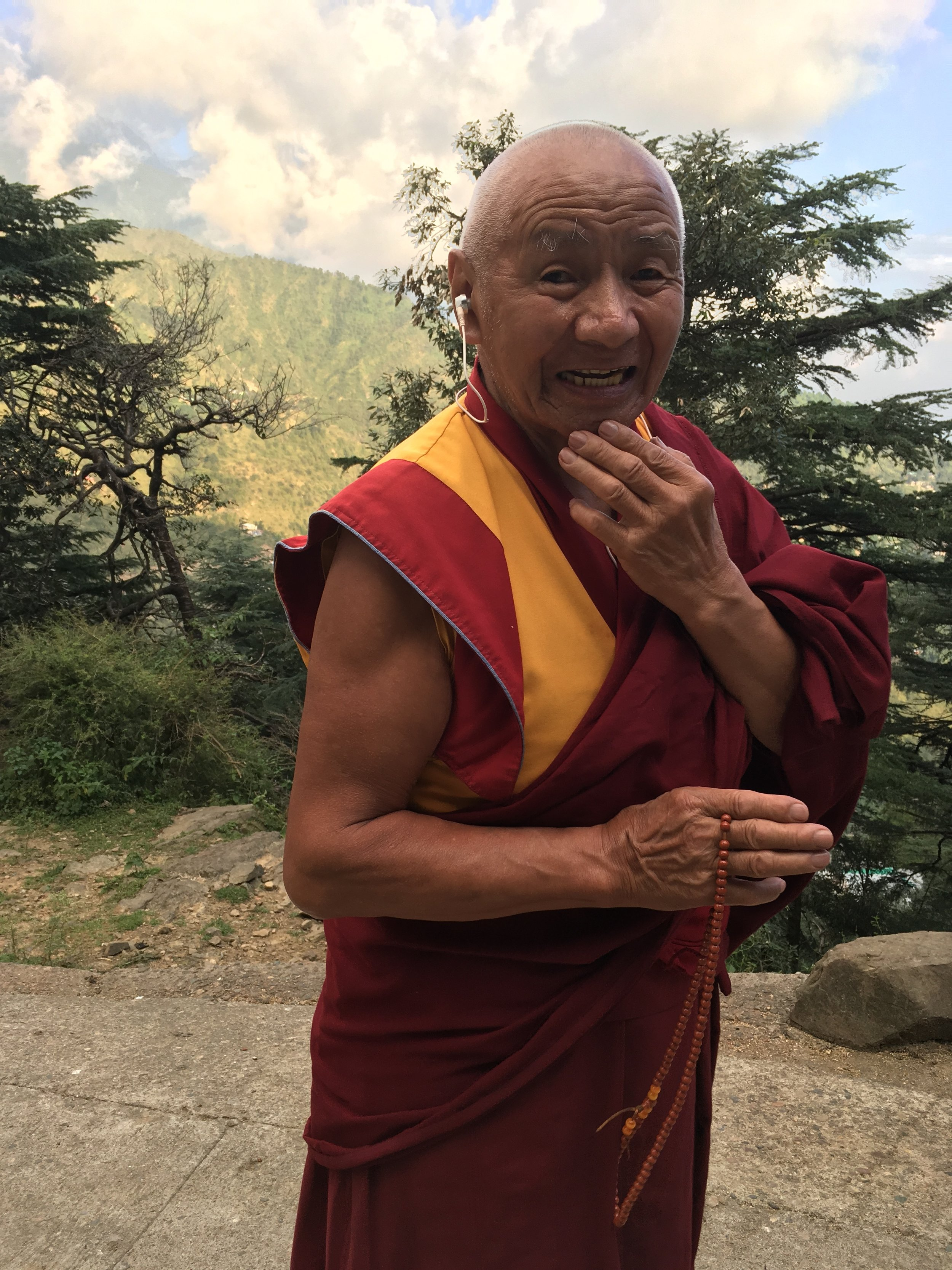 A monk pauses for a picture while on his meditation walk through a forested area near the Dalai Lama's temple in October 2018