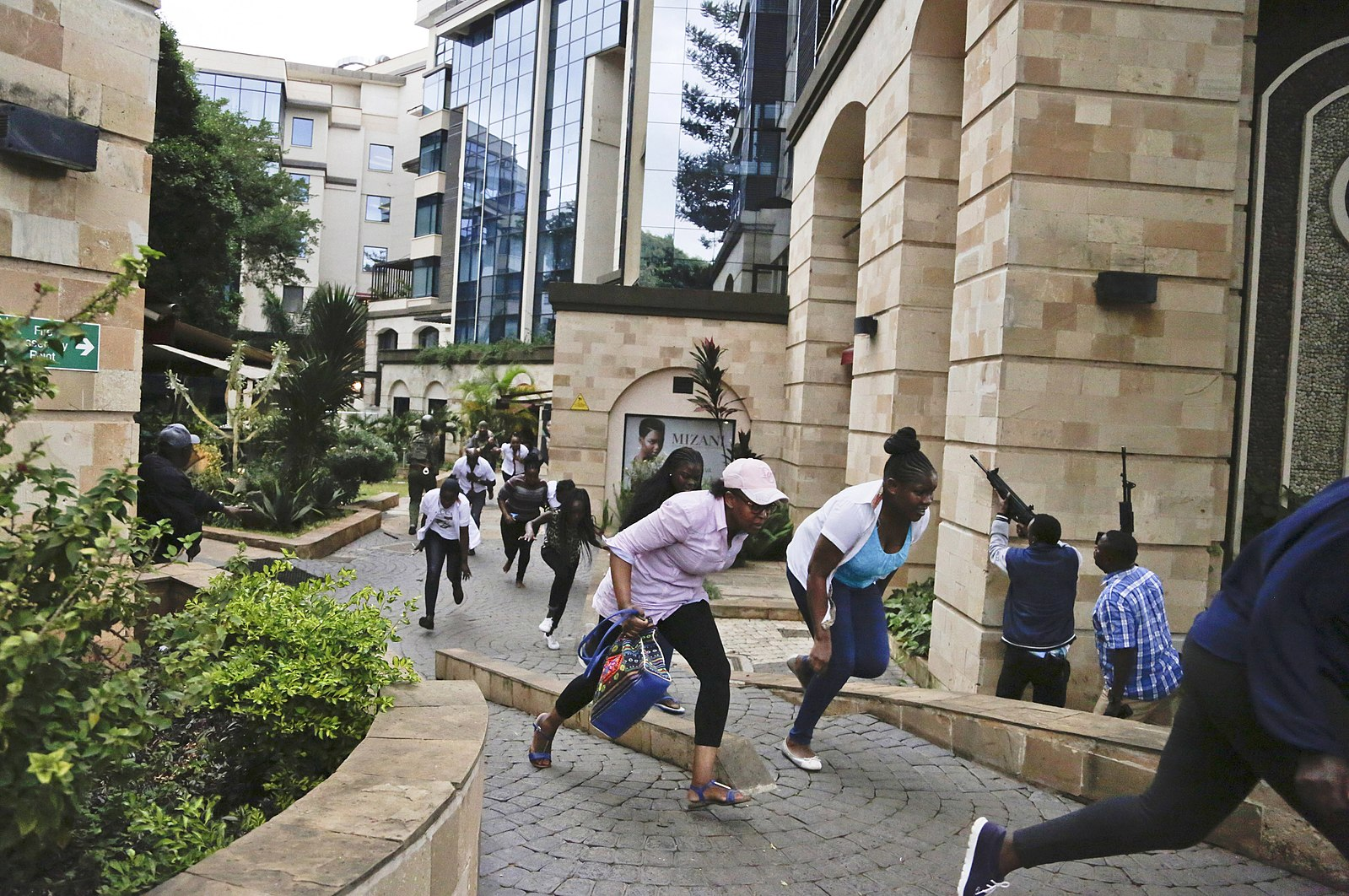 Guests flee a terrorist attack at the upscale Dusit hotel in Nairobi while plainclothes policemen enter the premises on Jan. 15, 2019. Photo by  Shadrack Kimutai .