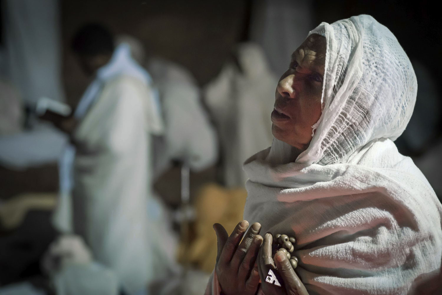 A Christian pilgrim with prayer beads on Christmas Eve night, at the rock church of Lalibela, Ethiopia. Photo by Chris Roche.