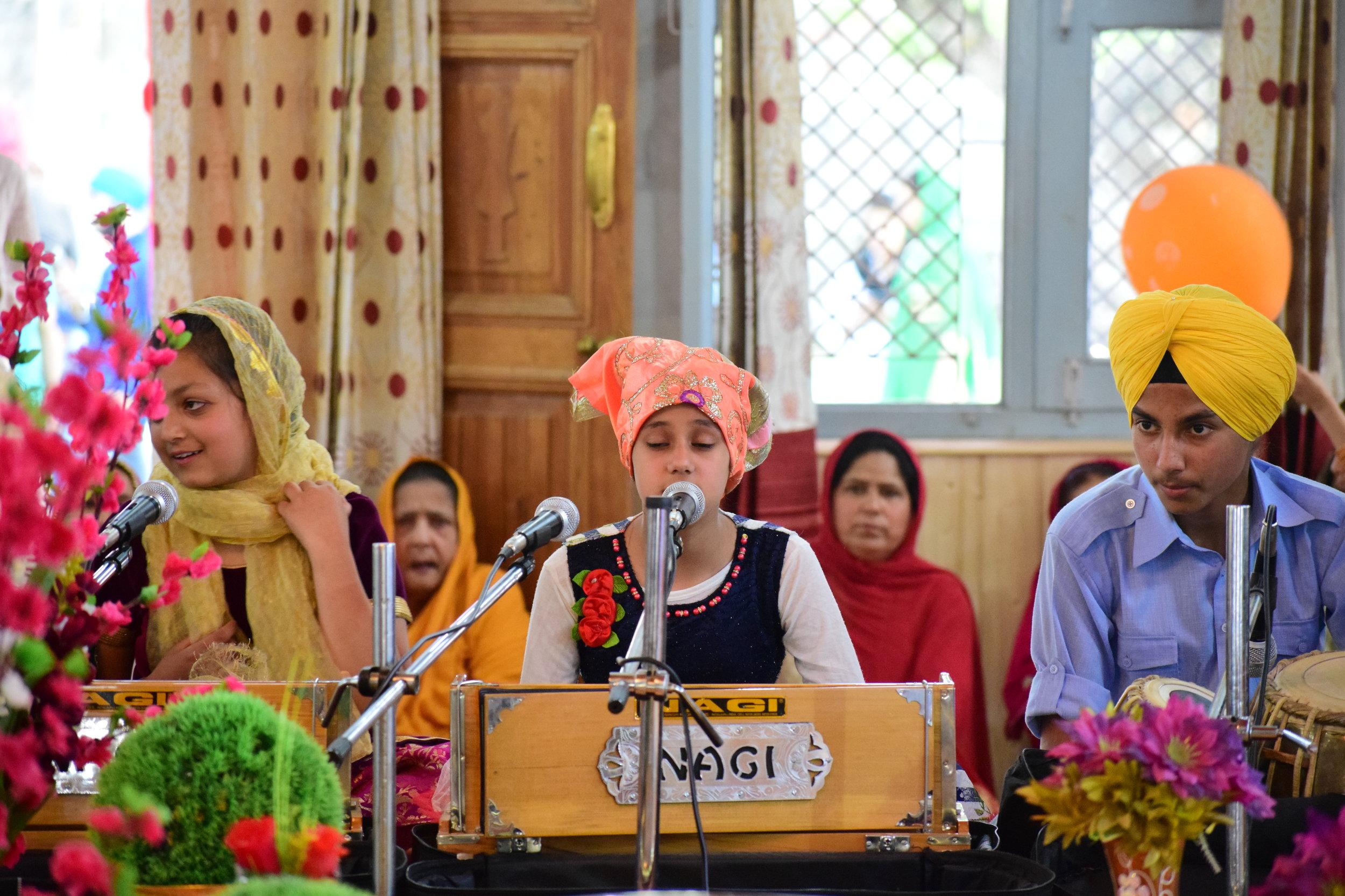 A young Kashmiri Sikh girl recites hymns during the celebrations of Guru Hargobind Singh's birthday. Photo by Karanjeet Singh.
