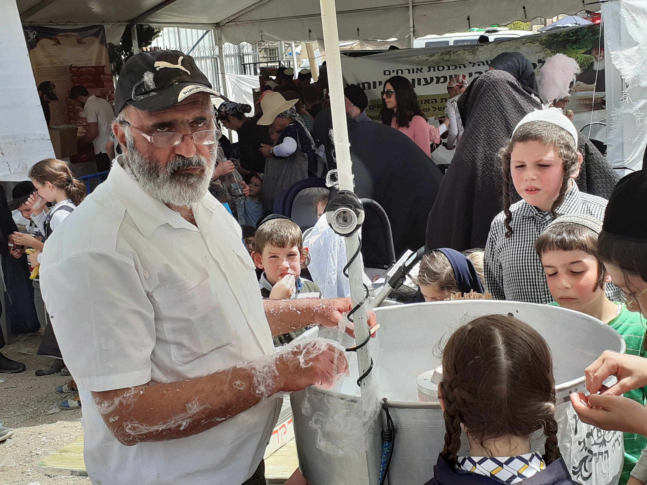 Kids watch a candy floss-maker during Lag b'Omer. Photo by Gil Zohar.