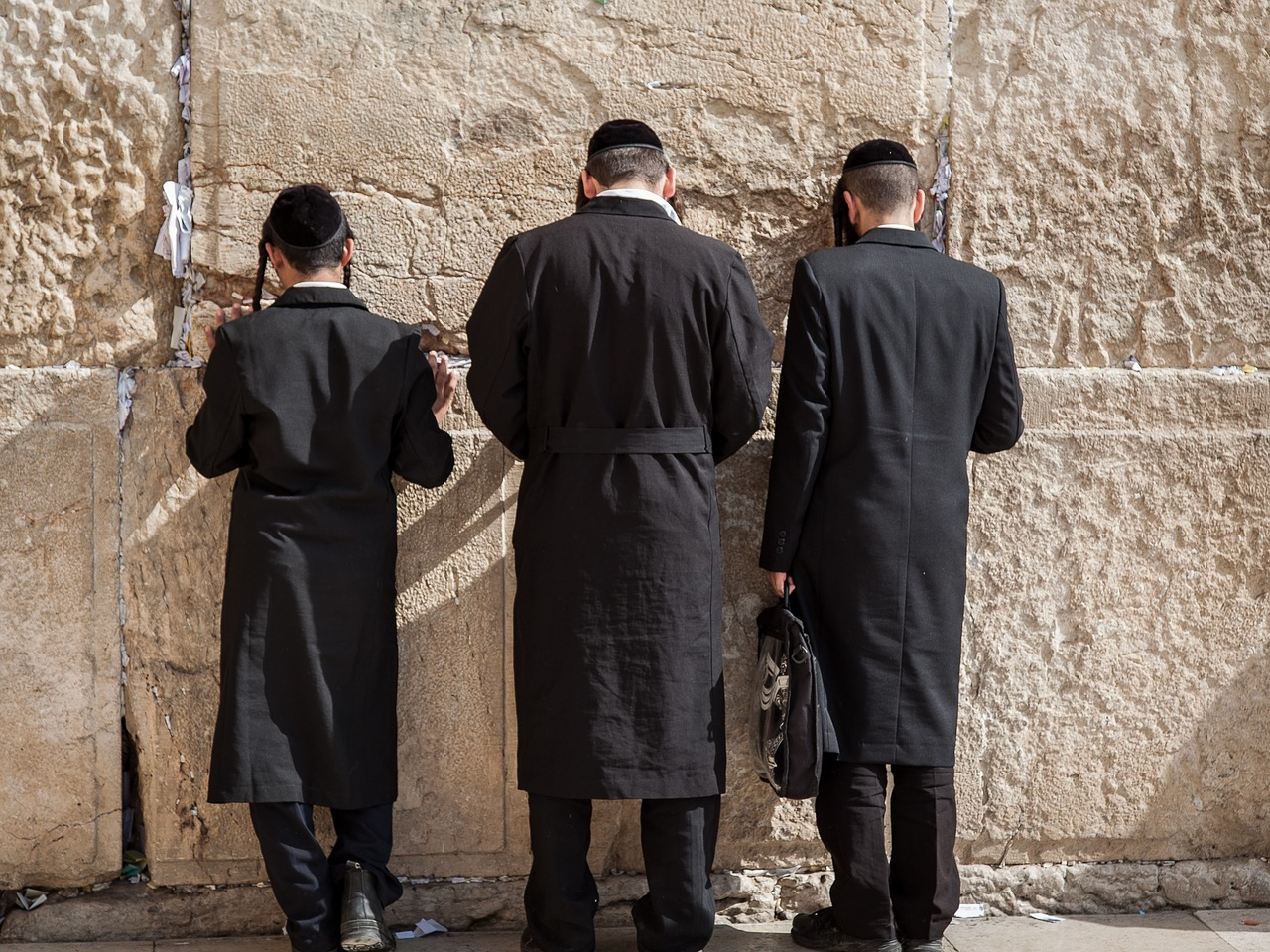 Three Jewish men pray at the Western Wall in Jerusalem. Creative Commons.