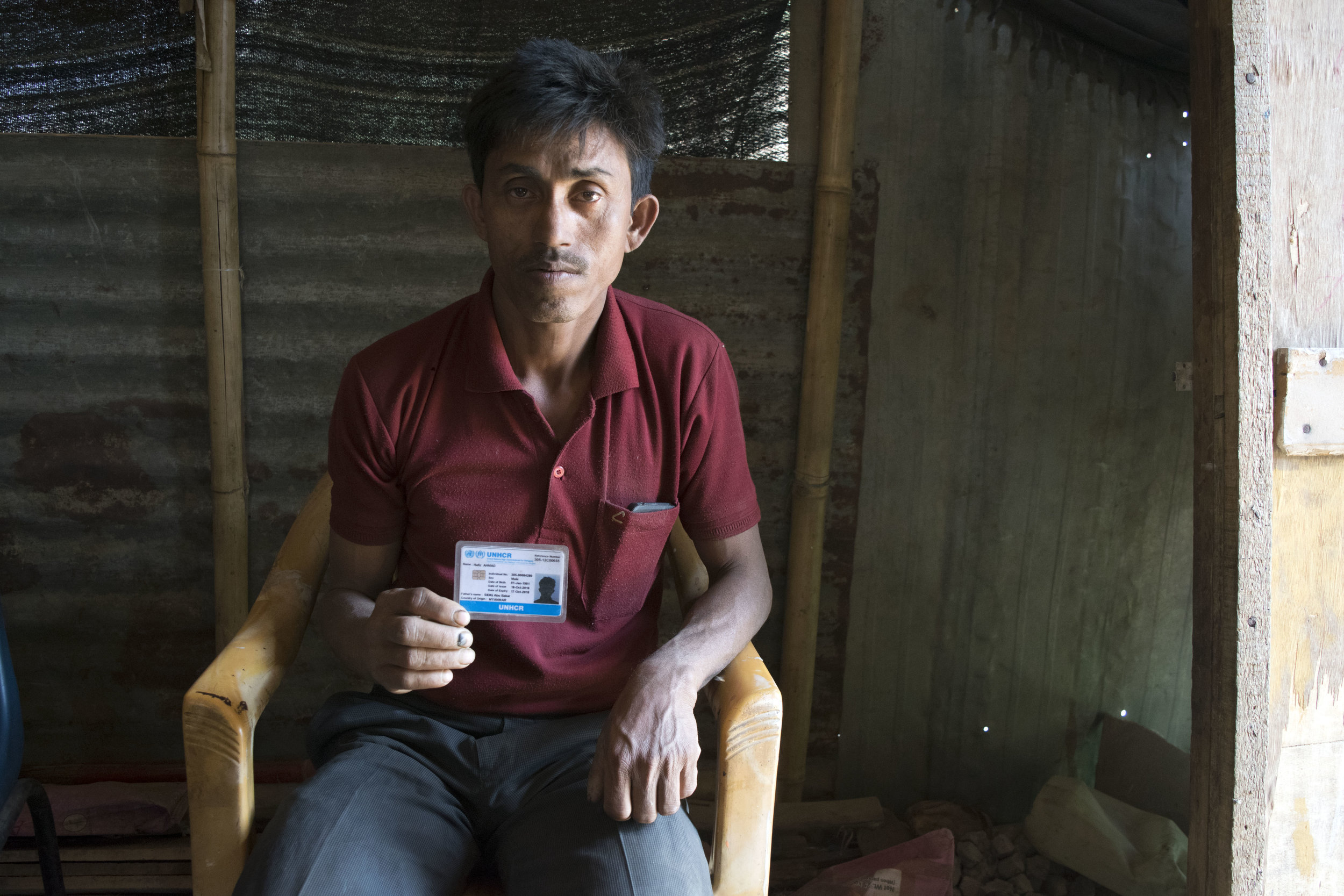 A Rohingya refugee holds up his UN-issued identity card, his only identity document as a stateless person. Photo by Meagan Clark.