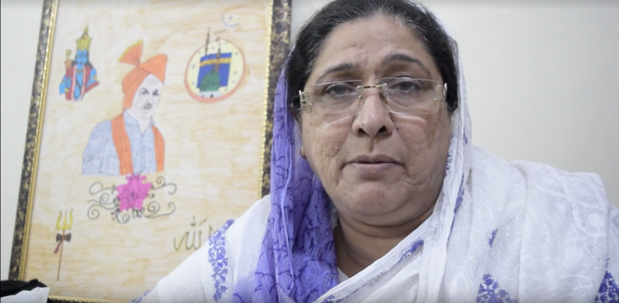 Shehnaz Afzal, head of the women's wing of the Muslim Rashtriya Manch, speaks in her office in Paharganj, Delhi. In the background, a student's illustration shows the Hindu god Ram (left), a mosque with the symbol for Islam (right) and a man donning a saffron turban (center), now generally a symbol of Hindu nationalism. Photo by Meagan Clark.