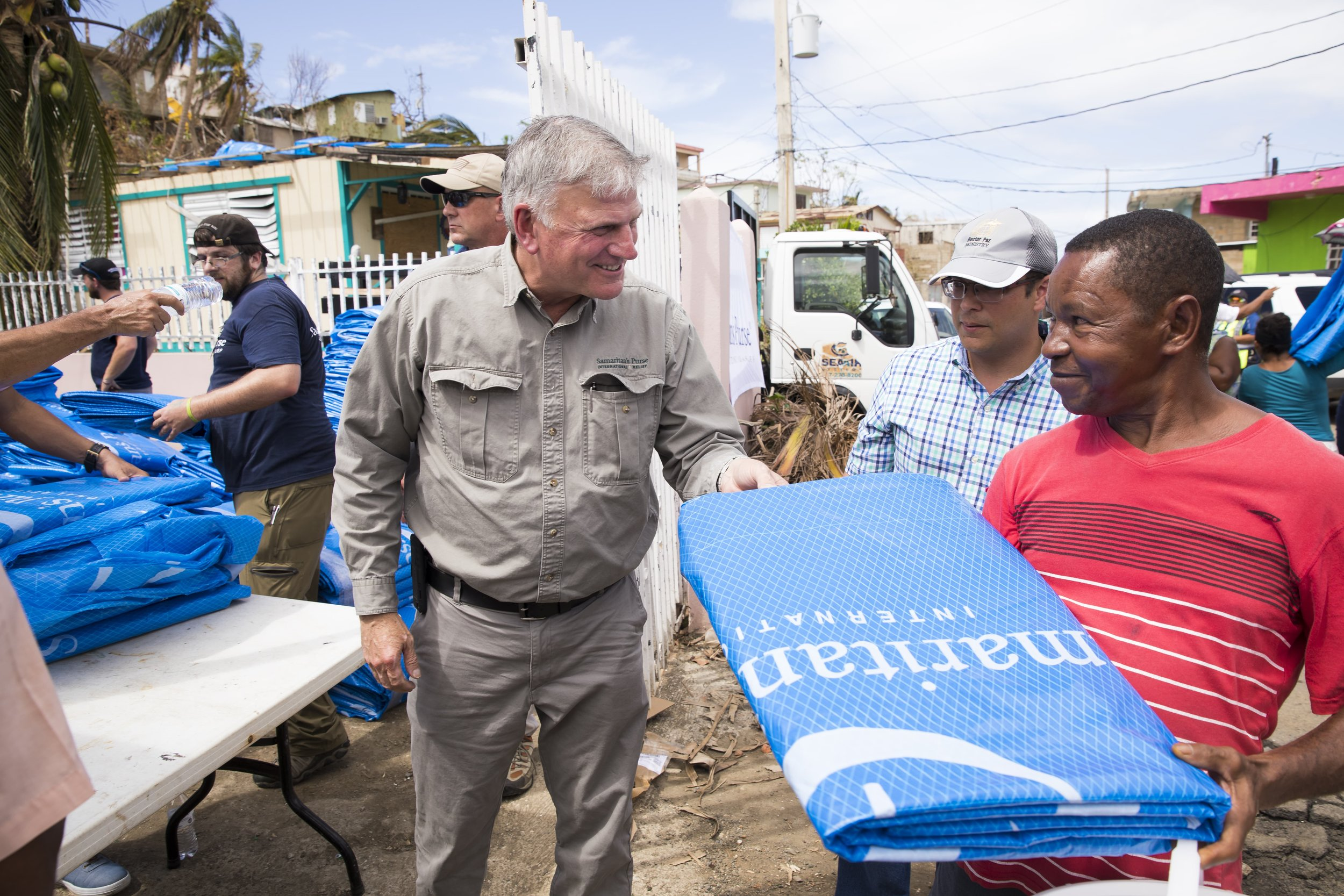 Franklin Graham distributes solar lights and tarp for emergency shelter to families in Puerto Rico devastated by Hurricane Maria. Photo courtesy of Samaritan's Purse.