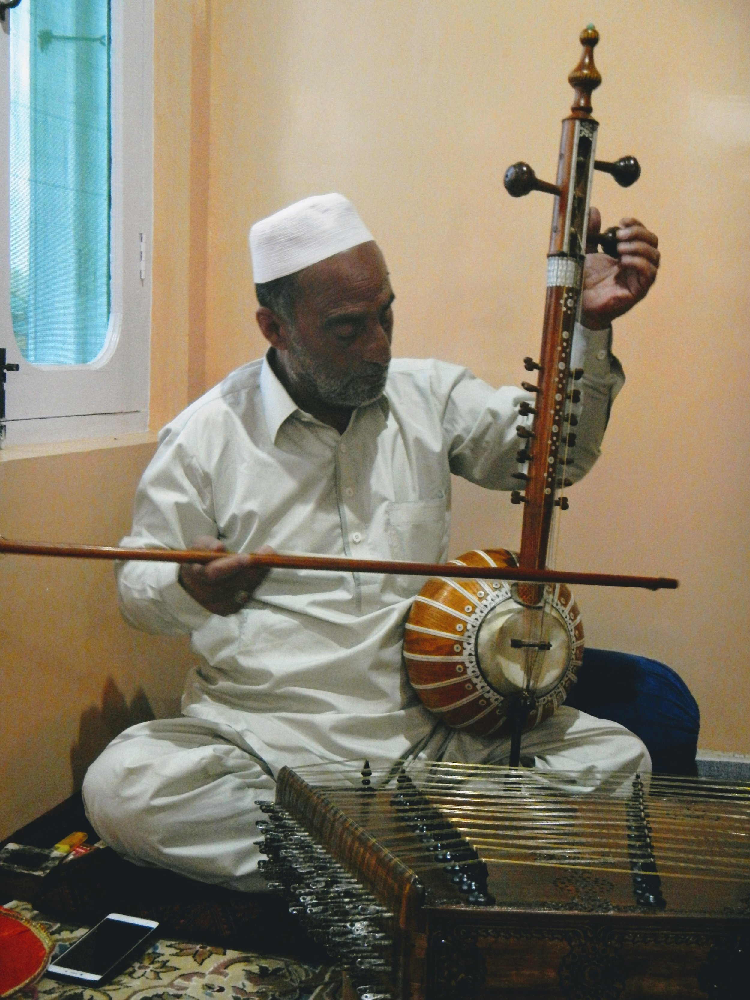Kashmiri classical music maestro Ustad Mohammad Yaqoob Sheikh before playing a composition by Jalaluddin Rumi in Srinagar, India. The santoor sits on the floor in the foreground, and Sheikh plays a Saz-e-Kashmir, a sort of pot-belly violin created in the region and distinctive to Kashmiri music. Photo by Priyadarshini Sen.