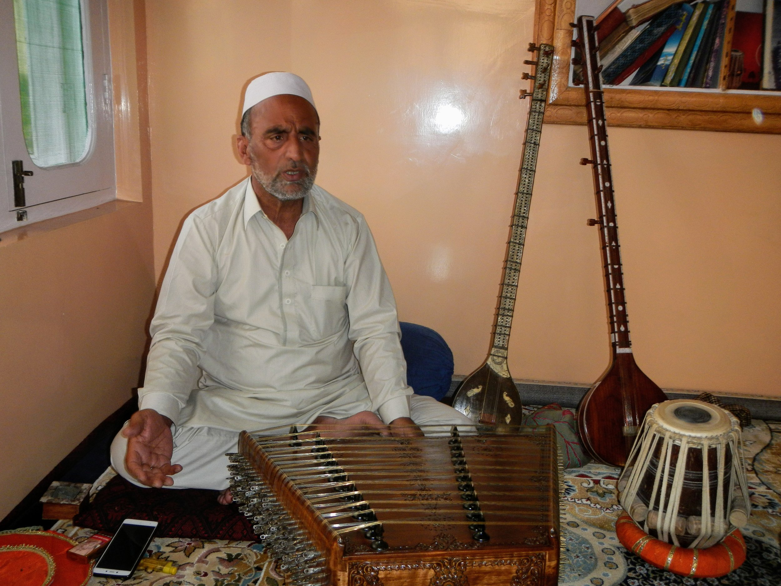 Kashmiri classical music maestro Ustad Mohammad Yaqoob Sheikh sits in front of his Saaz-e-Kashmir, a traditional instrument used in Sufiana ensembles in Srinagar, India. Photo by Priyadarshini Sen.