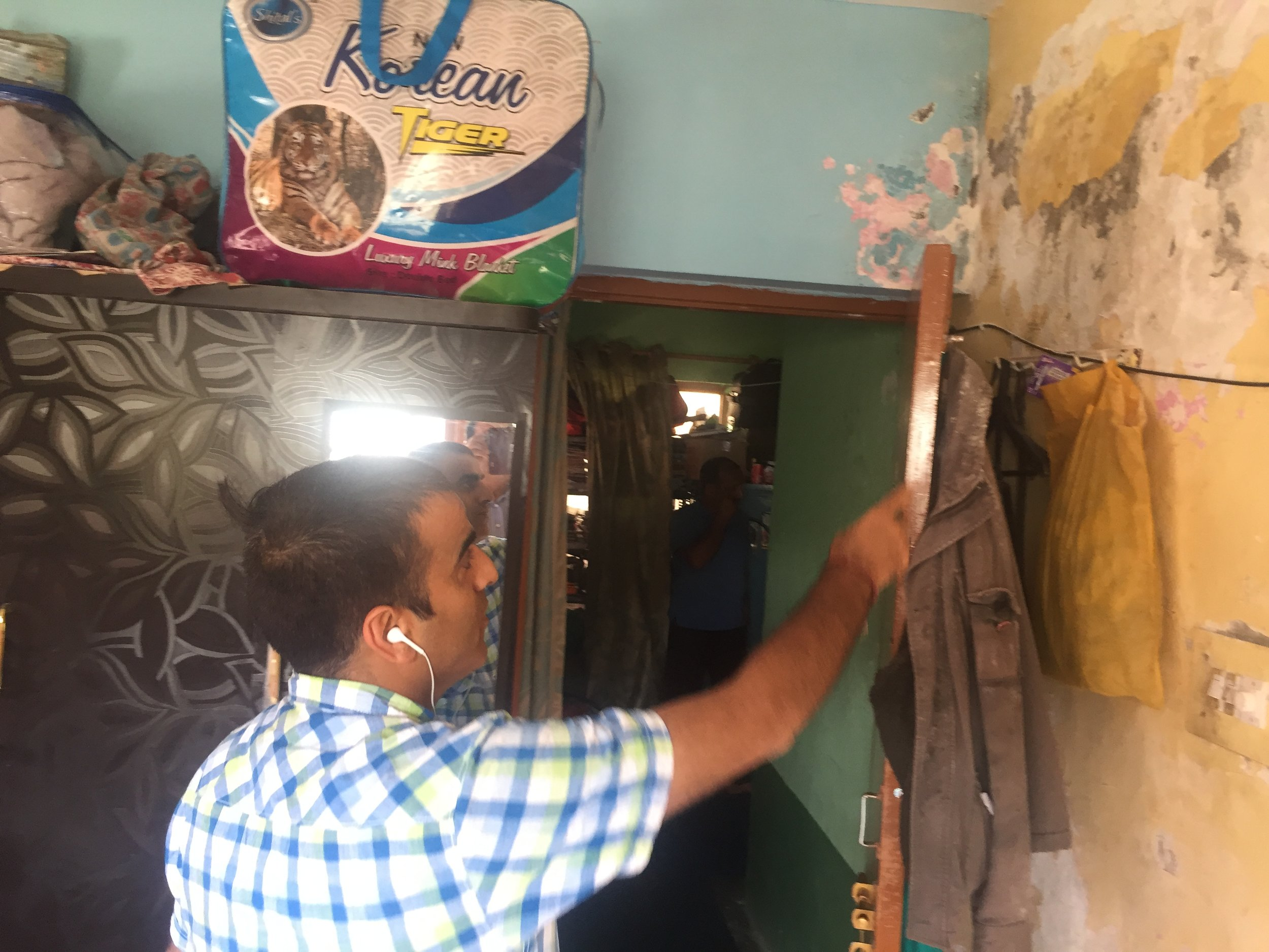 A Kashmiri Pandit showing how his walls are sopping wet due to leaking sewage pipes in his apartment in Budgam, Kashmir. Photo by Taha Zahoor.