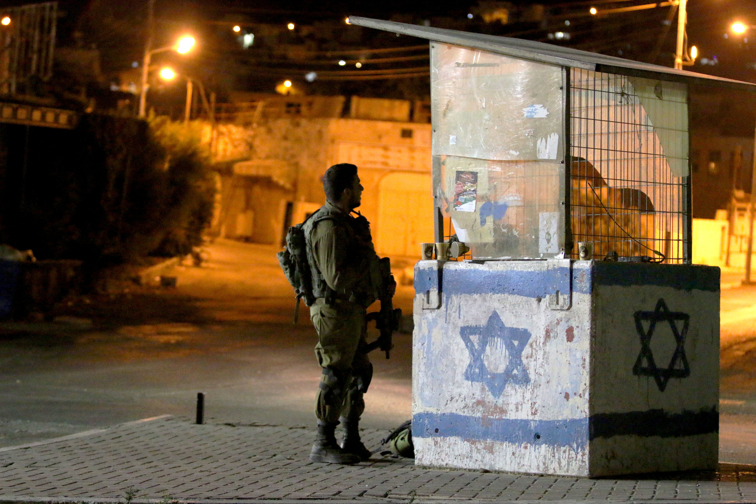 An Israeli soldier stands at his post in the West Bank city of Hebron. Photo by Micah Danney.