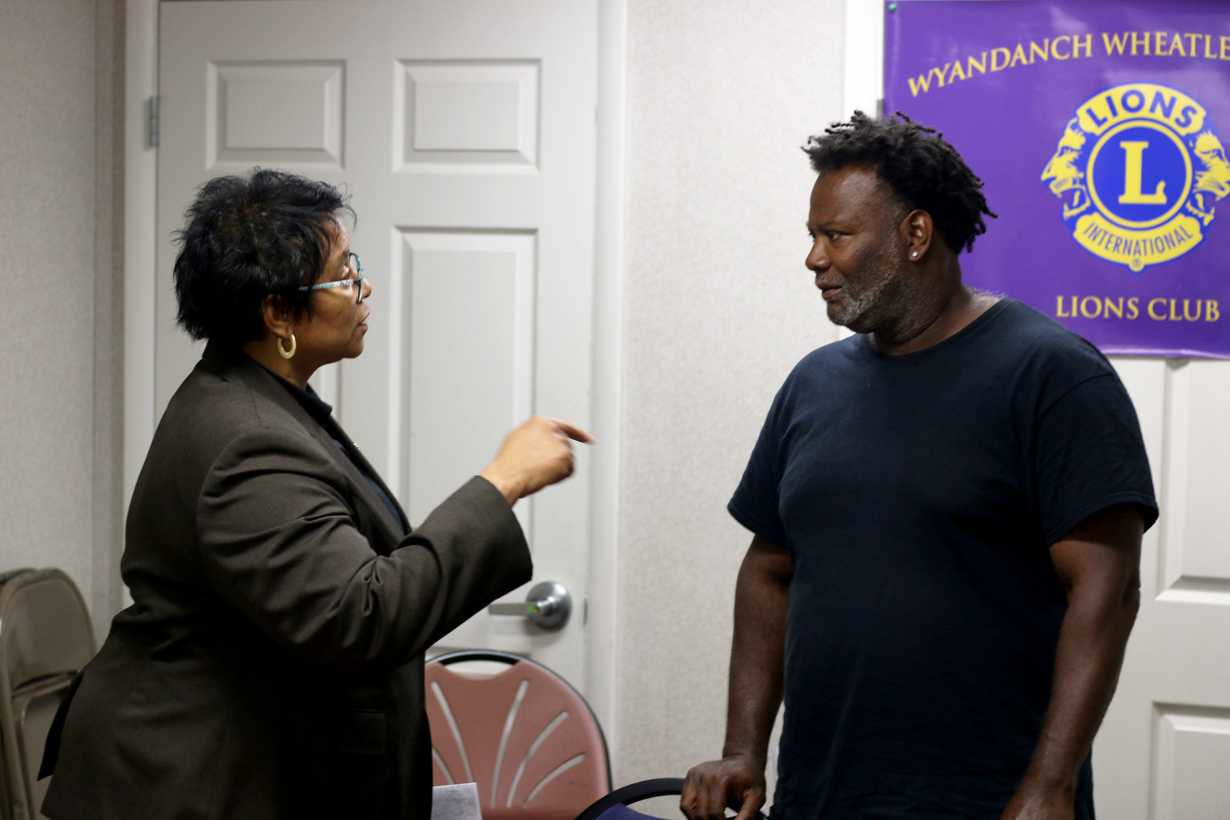 Mention-Lewis speaks to Yazid Owens, a facilitator of the Wyandanch meeting. Photo by Micah Danney.