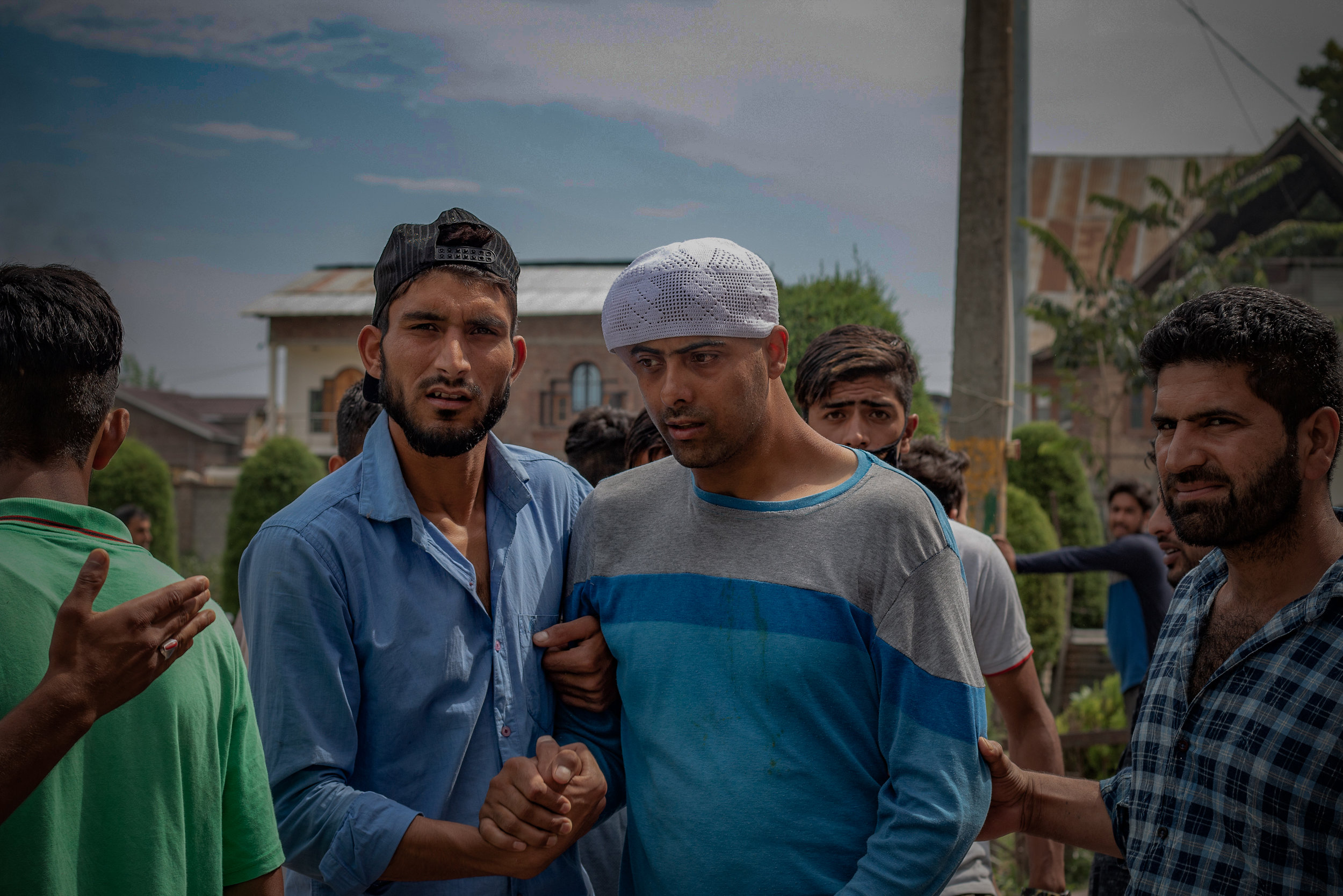 "The man wearing the skull cap (in the center) was shot at by Indian security personnel with a full cartridge of lead pellets in 2018. ""He remained in the ICU for 15 months,"" his brother, Mehrazudin War, said. The victim, who is still unable to walk without support, came to greet the protestors. Photo by Avinash Giri."