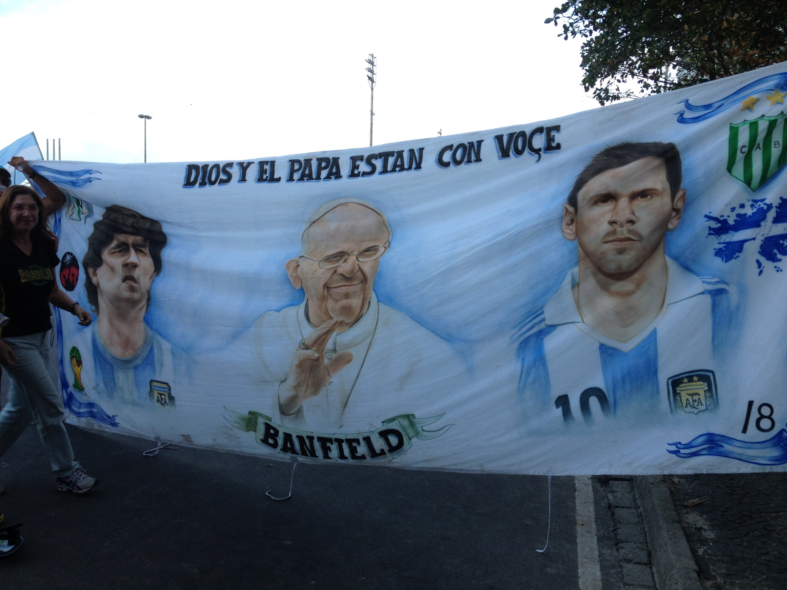 Argentina fans unfurl a banner during the 2014 World Cup featuring three Argentine stars: Pope Francis in the center, flanked by soccer stars Diego Maradona (left) and Lionel Messi (right). Photo by Clemente Lisi.